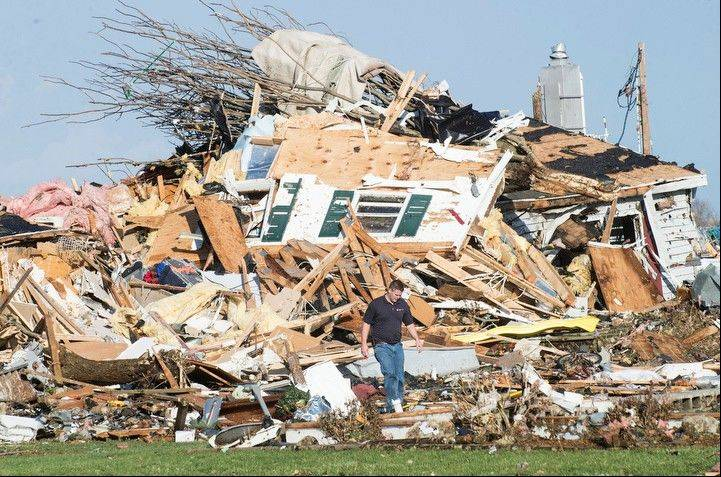 A man walks through a damaged home in Gifford, Ill. on Sunday, Nov. 17, 2013. Intense thunderstorms and tornadoes swept across the Midwest, causing extensive damage in several central Illinois communities while sending people to their basements for shelter.