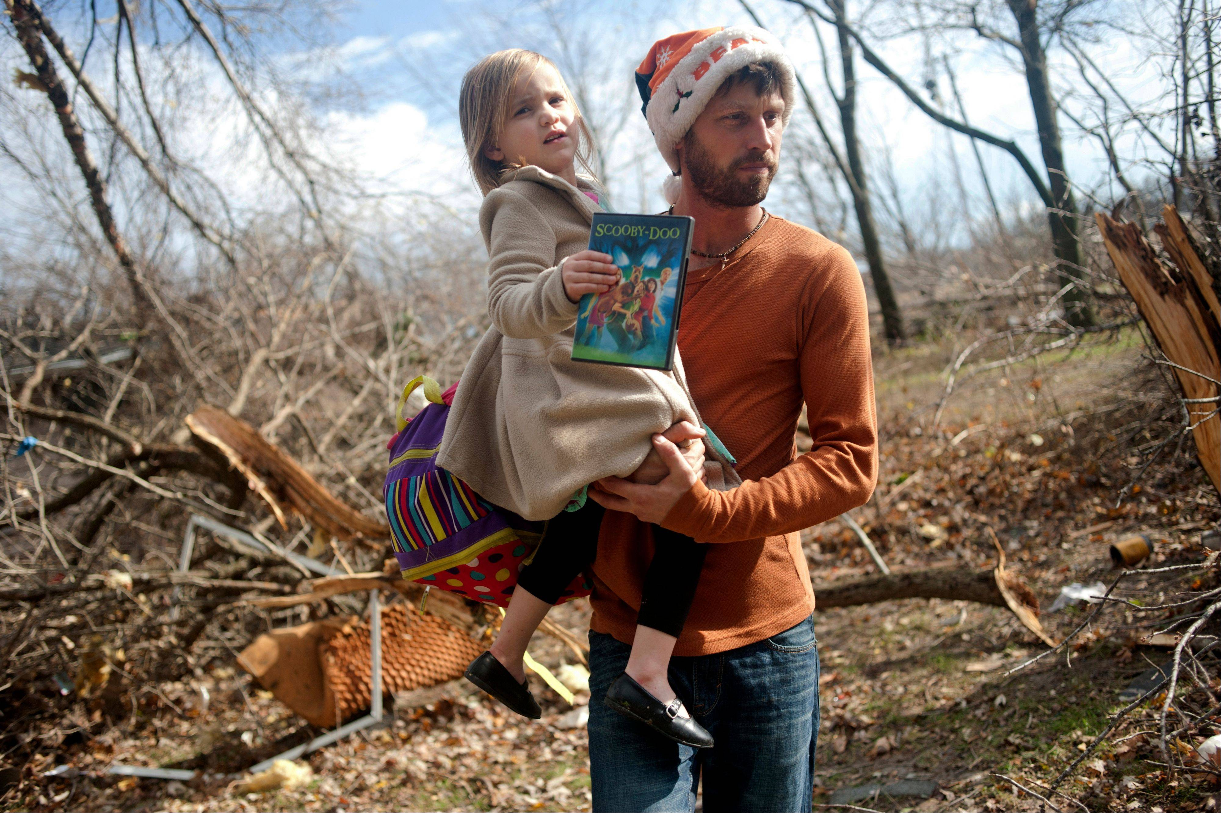 East Peoria resident Billy Vestal evacuates with his daughter, Lillian Vestal, 3, after a tornado damaged the area near Chestnut Road in East Peoria, Il.,Sunday, Nov. 17, 2013. Intense thunderstorms and tornadoes swept across the Midwest on Sunday, causing extensive damage in several central Illinois communities while sending people to their basements for shelter.