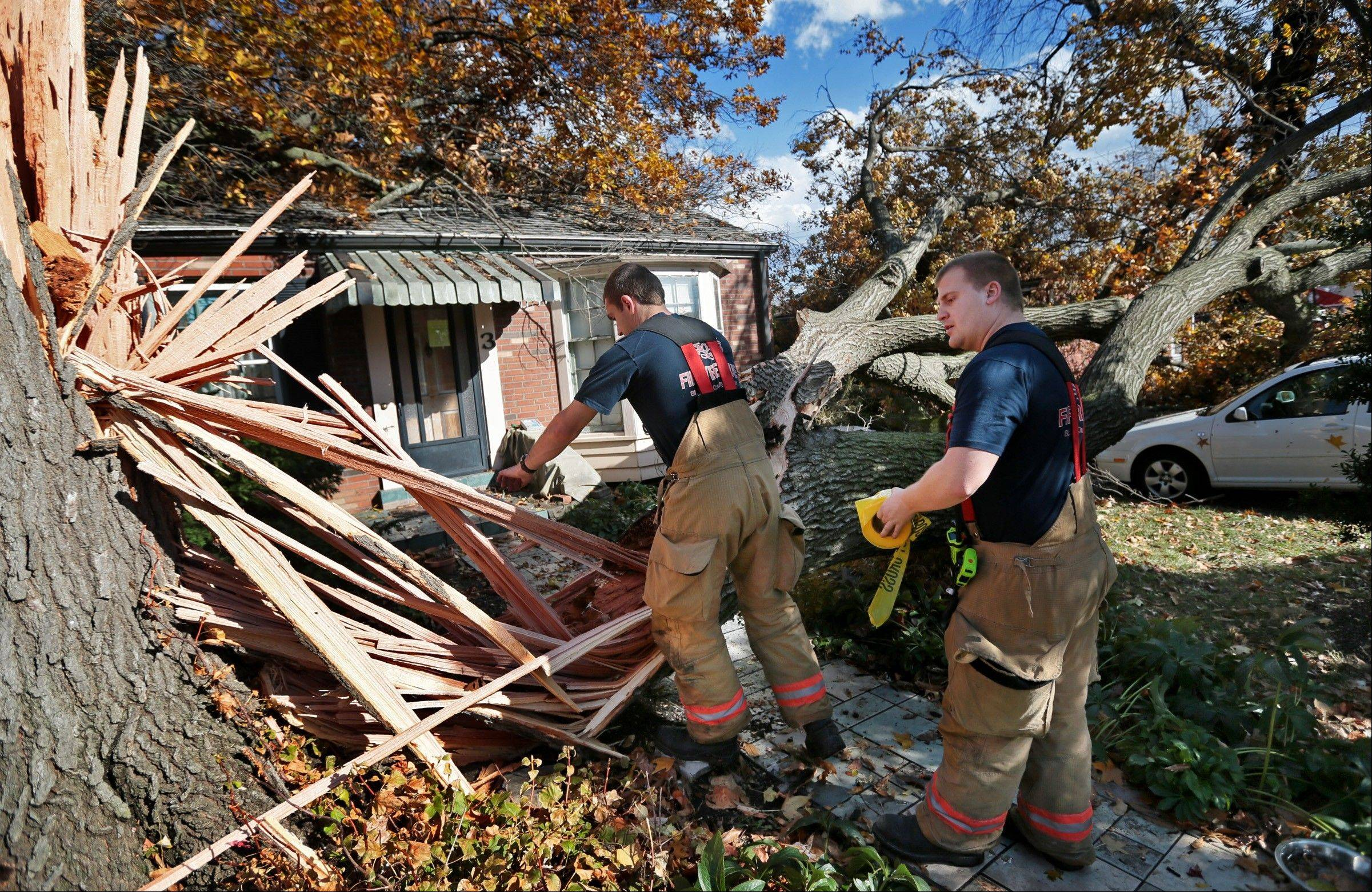 Webster Groves firefighters Chris Manita, center, and Matt Grossenhieder climb over a tree that fell on a house on Clydehurst Drive in Webster Groves, Mo., Sunday, Nov. 17, 2013. The residents of the house were home at the time the tree fell but were not injured. Intense thunderstorms and tornadoes swept across a number of Midwestern states Sunday, causing damage in several central Illinois communities while sending people to their basements for shelter and even prompting officials at Soldier Field in Chicago to evacuate the stands and delay the Bears game.