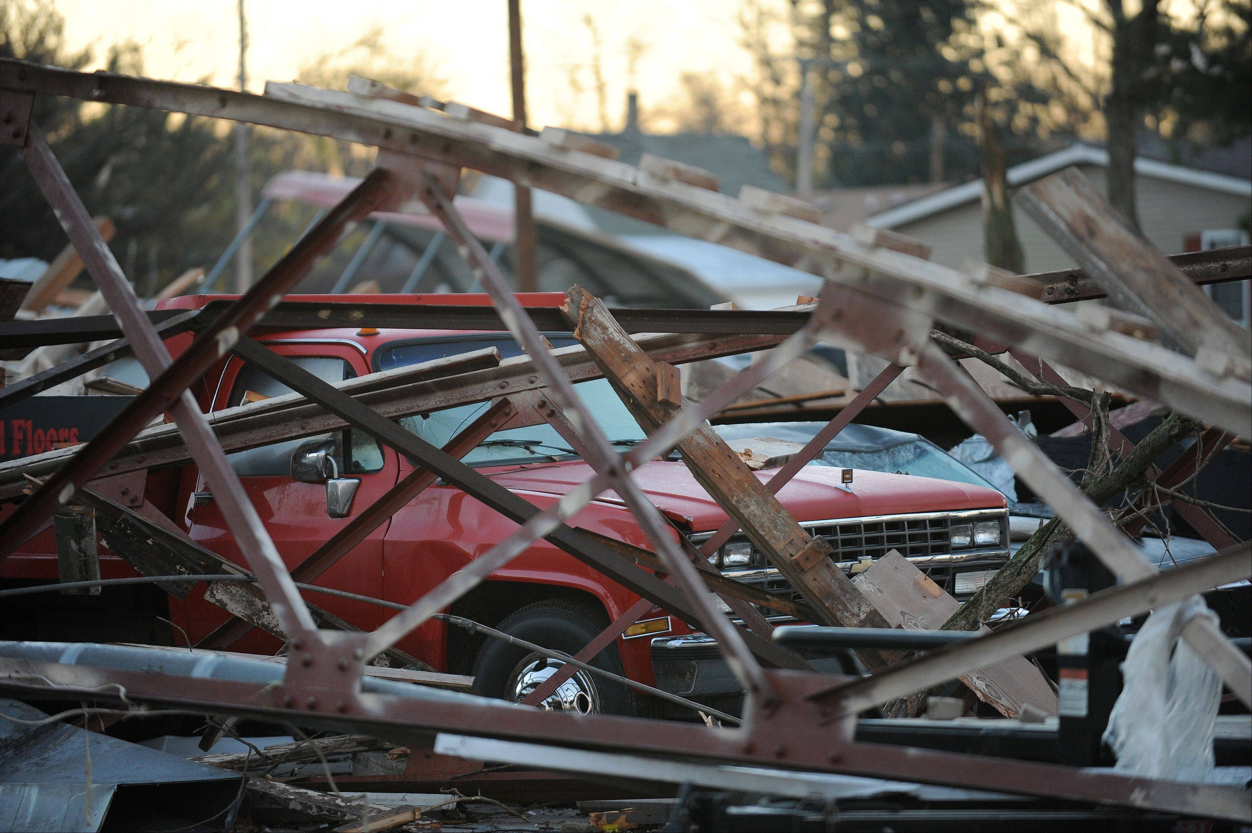 A pick-up truck is buried under storm debris in Brookport, Ill., Monday, Nov. 18, 2013. Dozens of tornadoes and intense thunderstorms swept across the U.S. Midwest on Sunday, unleashing powerful winds that flattened entire neighborhoods, flipped over cars and uprooted trees.