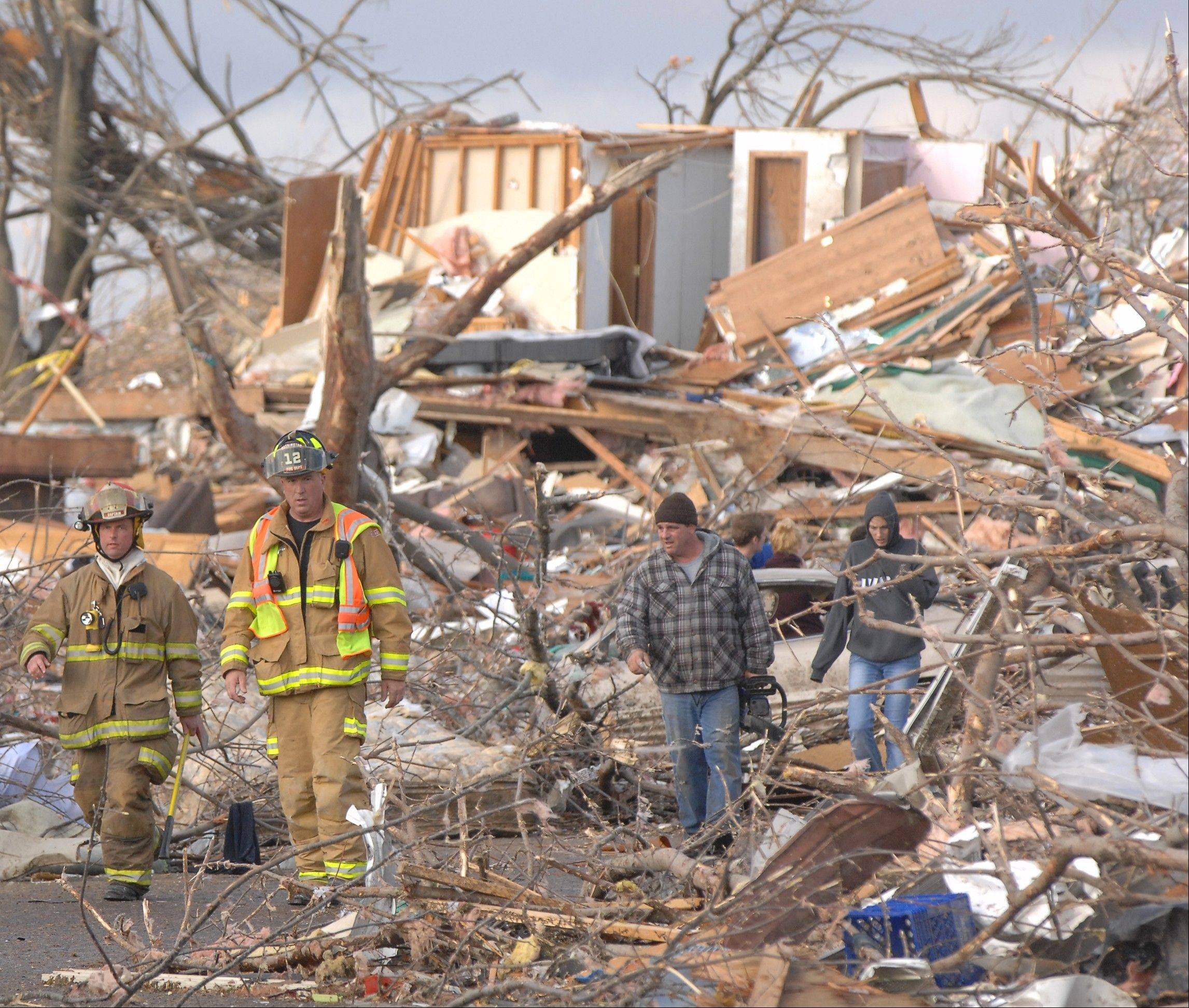 Washington firefighters survey Devonshire Street on the North side of Washington, Ill., Sunday, Nov. 17, 2013. Intense thunderstorms and tornadoes swept across the Midwest, causing extensive damage in several central Illinois communities while sending people to their basements for shelter.