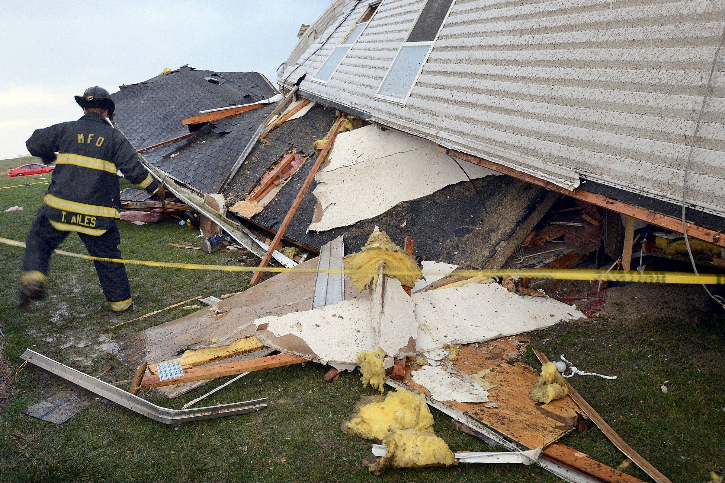 A Marion firefighter steps around wind-damaged trailers at Summit Village east of Marion, Ind., after storms blew through Marion and Grant County on Sunday afternoon, Nov. 17, 2013.