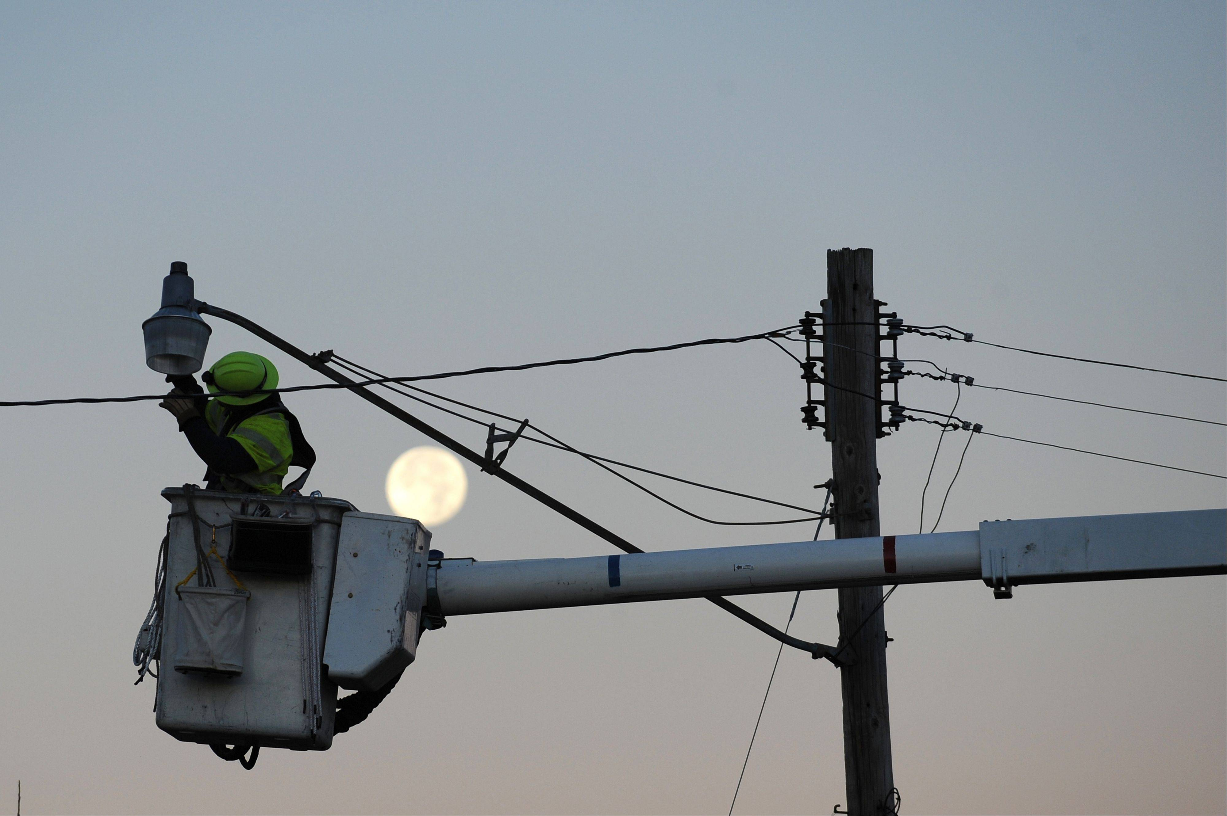 The moon is seen behind a utility worker repairing a city street light in Brookport, Ill., Monday, Nov. 18, 2013. Dozens of tornadoes and intense thunderstorms swept across the U.S. Midwest on Sunday, unleashing powerful winds that flattened entire neighborhoods, flipped over cars and uprooted trees.