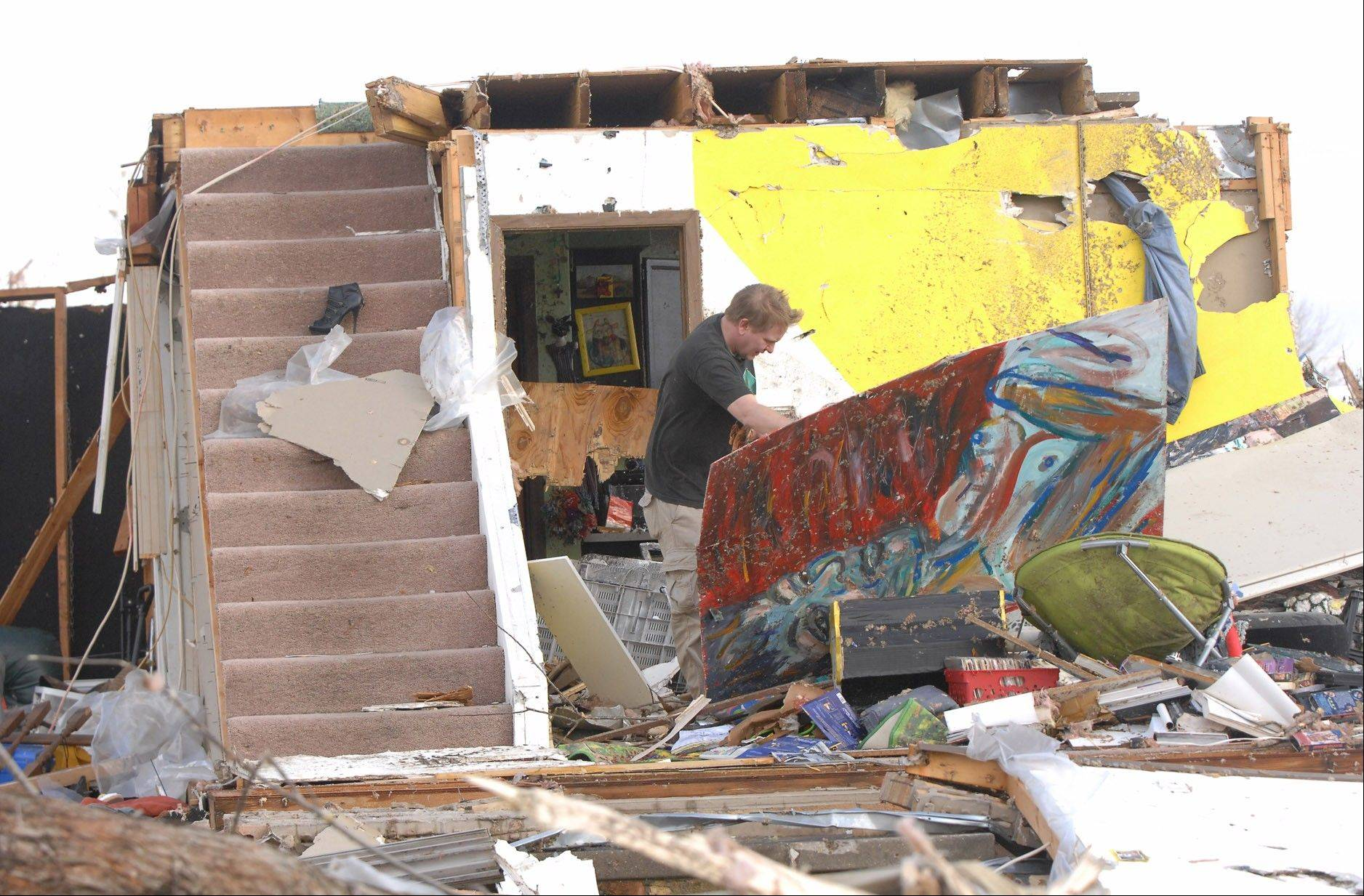 A Washington homeowner moves debris next to a set of stairs that once lead to the second floor of his home in Washington, Ill., Sunday, Nov. 17, 2013. Intense thunderstorms and tornadoes swept across the Midwest, causing extensive damage in several central Illinois communities while sending people to their basements for shelter.