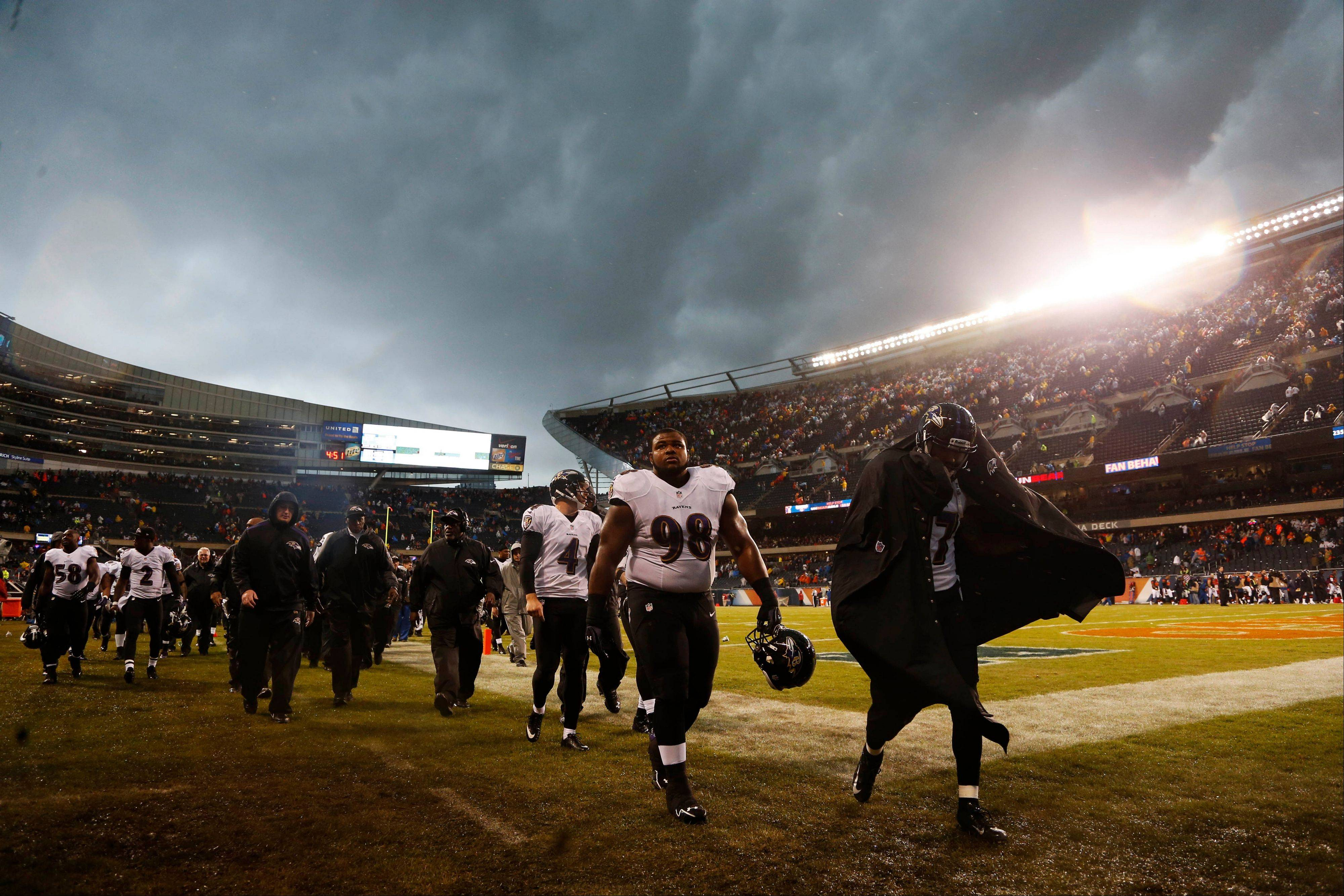Baltimore Ravens players leave the field as play was suspended for a severe thunderstorm blowing through Soldier Field during the first half of an NFL football game Sunday against the Chicago Bears in Chicago. The Bears would go on to win 23-20 in overtime.