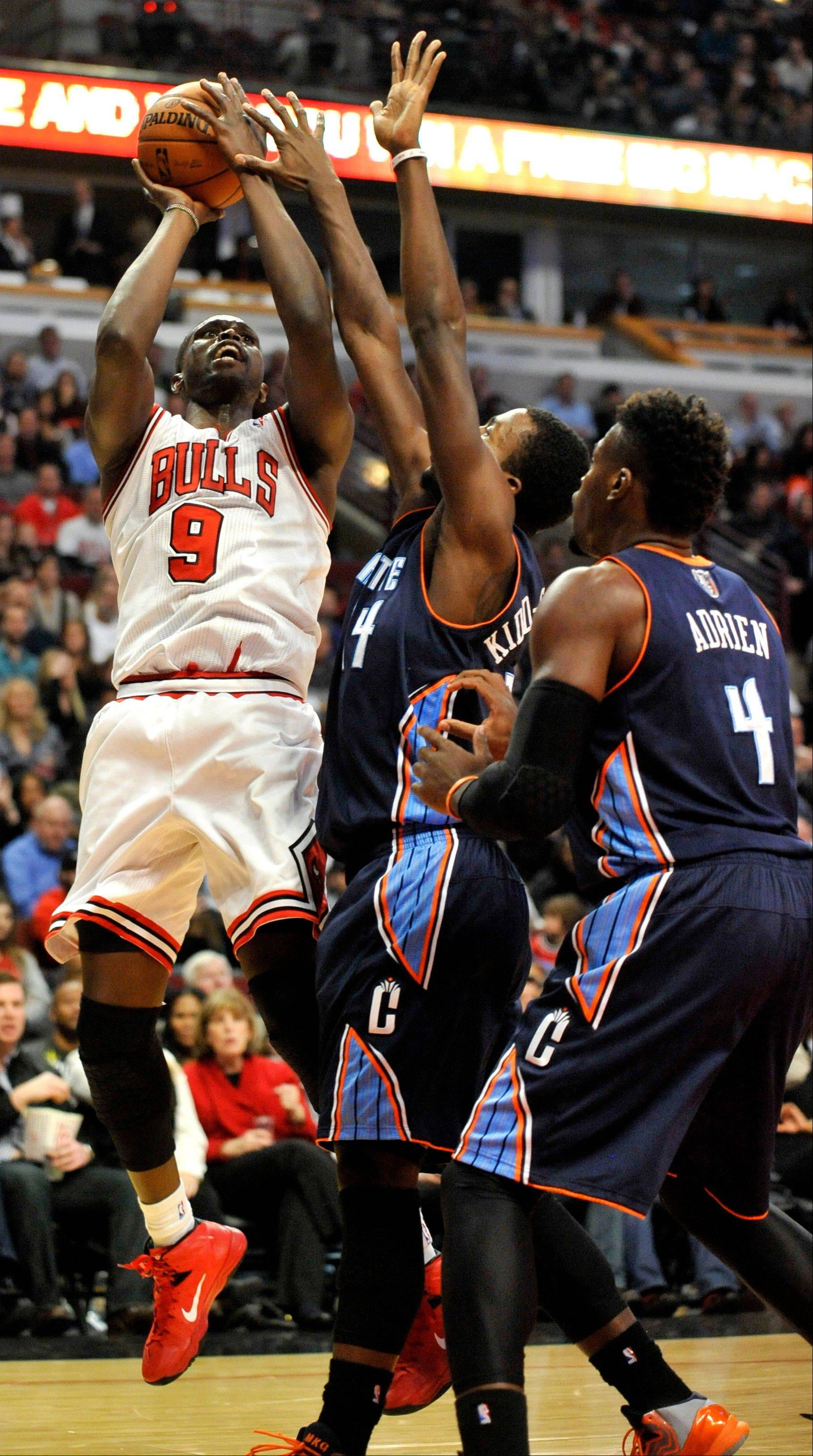 The Bulls' Luol Deng goes up for a shot against Charlotte's Michael Kidd-Gilchrist (14) and Jeff Adrien (4) during the second quarter of Monday's game in Chicago.
