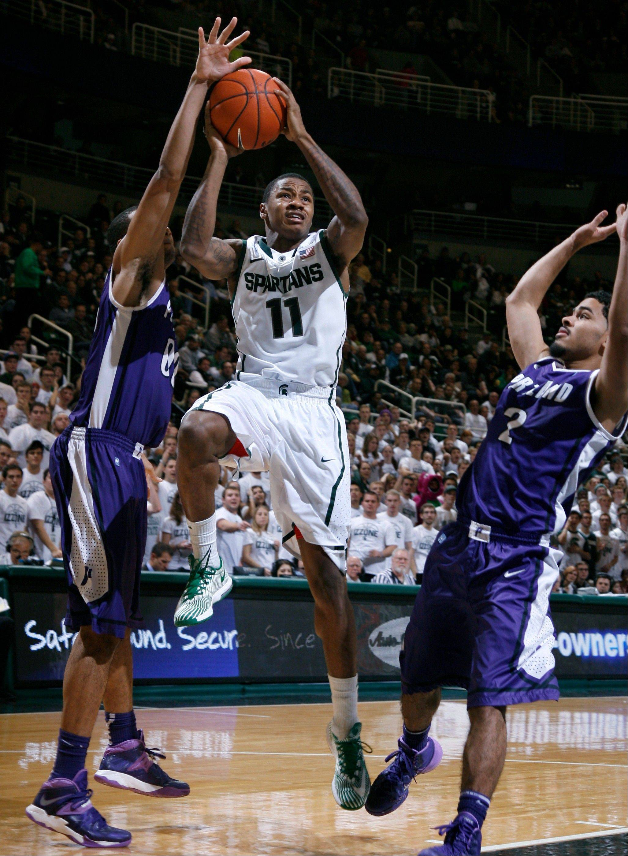 Michigan State's Keith Appling drives between Portland's Kevin Bailey, left, and Alec Wintering during the second half of Monday's game in East Lansing, Mich.