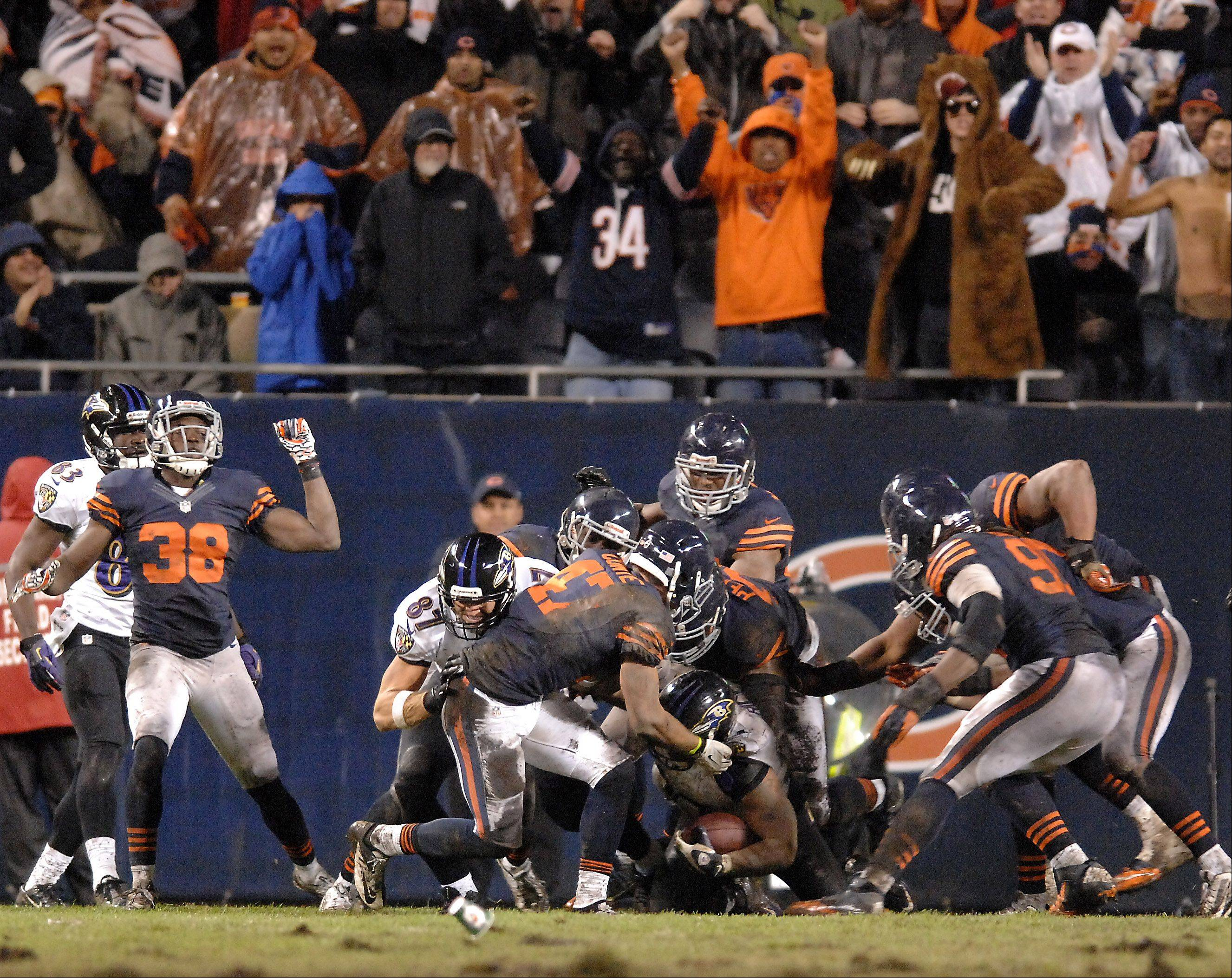 The Bears' defense stops running back Ray Rice near the goal line as they hold the Ravens to a field goal at the end of regulation Sunday.