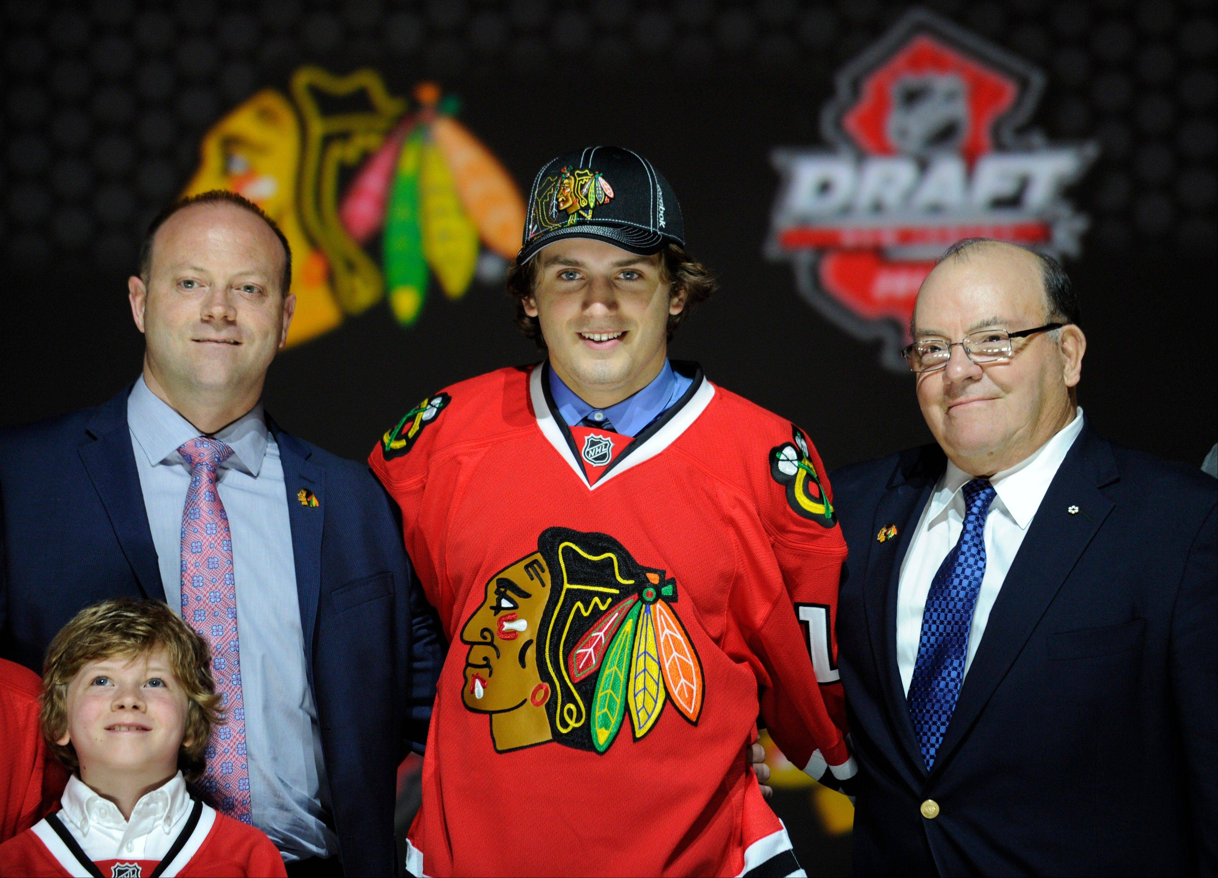 Ryan Hartman, a winger, stands with officials from the Chicago Blackhawks sweater after being chosen 30th overall in the first round of the NHL hockey draft, Sunday, June 30, 2013, in Newark, N.J.