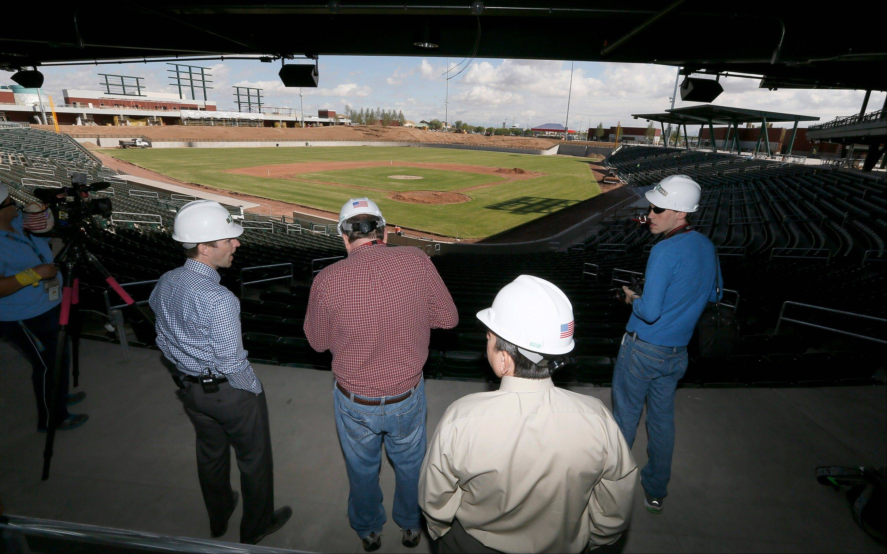 Justin Piper, left, Chicago Cubs general manager of spring training operations, shows members of the media the new stadium under construction at the team's new spring training facility on Thursday, Oct. 10, 2013, in Mesa, Ariz. The facility is scheduled to be open for next year's spring training.