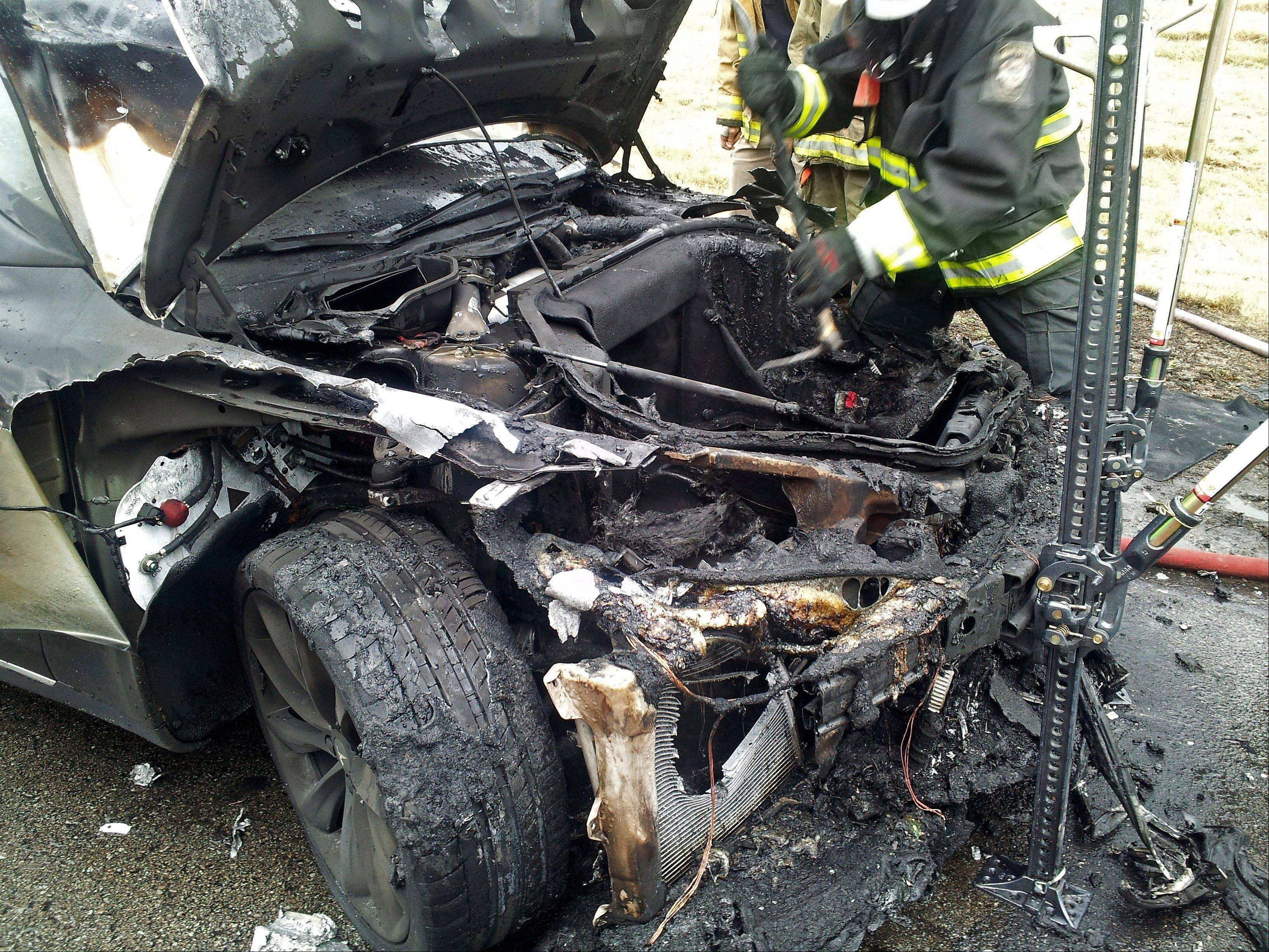Emergency workers respond to a fire on a Tesla Model S electric car in Smyrna, Tenn., in this file photo from Nov. 6. The National Highway Traffic Administration has opened an investigation into battery fires in Tesla Model S electric cars.