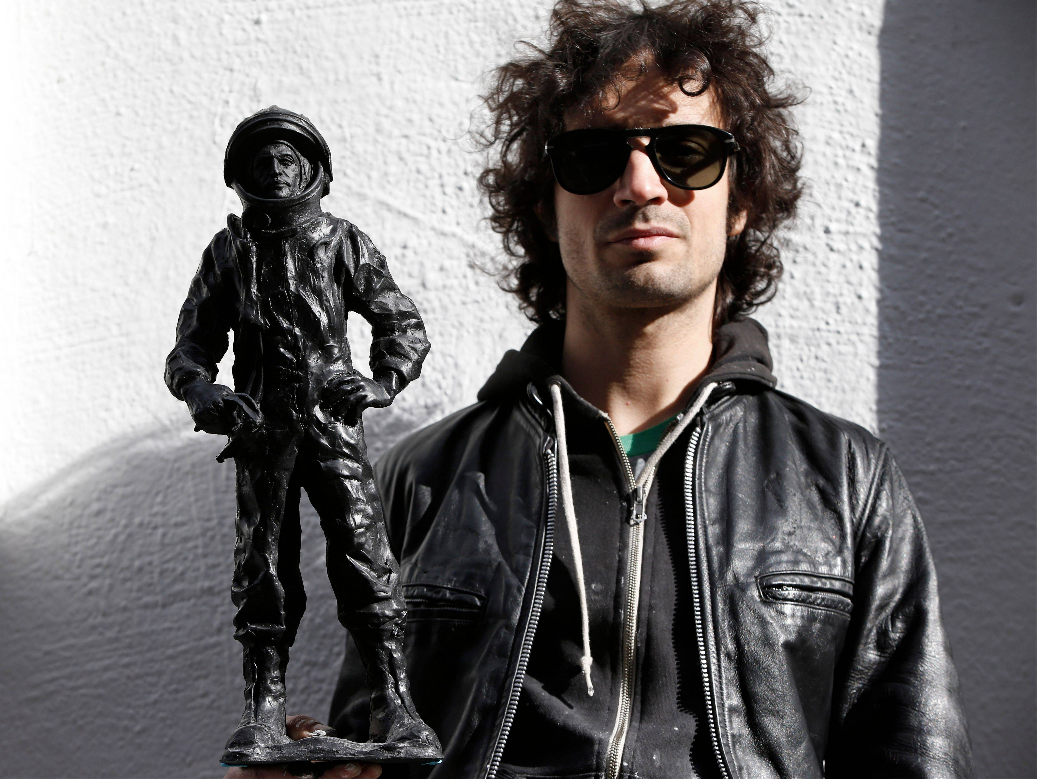 The Strokes' drummer Fabrizio Moretti with one of his cast-in-plastic astronauts beside the SoHo Rag & Bone store where his art is installed in New York. Moretti's installation at one time included white niches filled with white plastic astronauts, but they were all stolen. Moretti created new black astronauts but relocated the new pieces to a second-story fire escape above the installation.