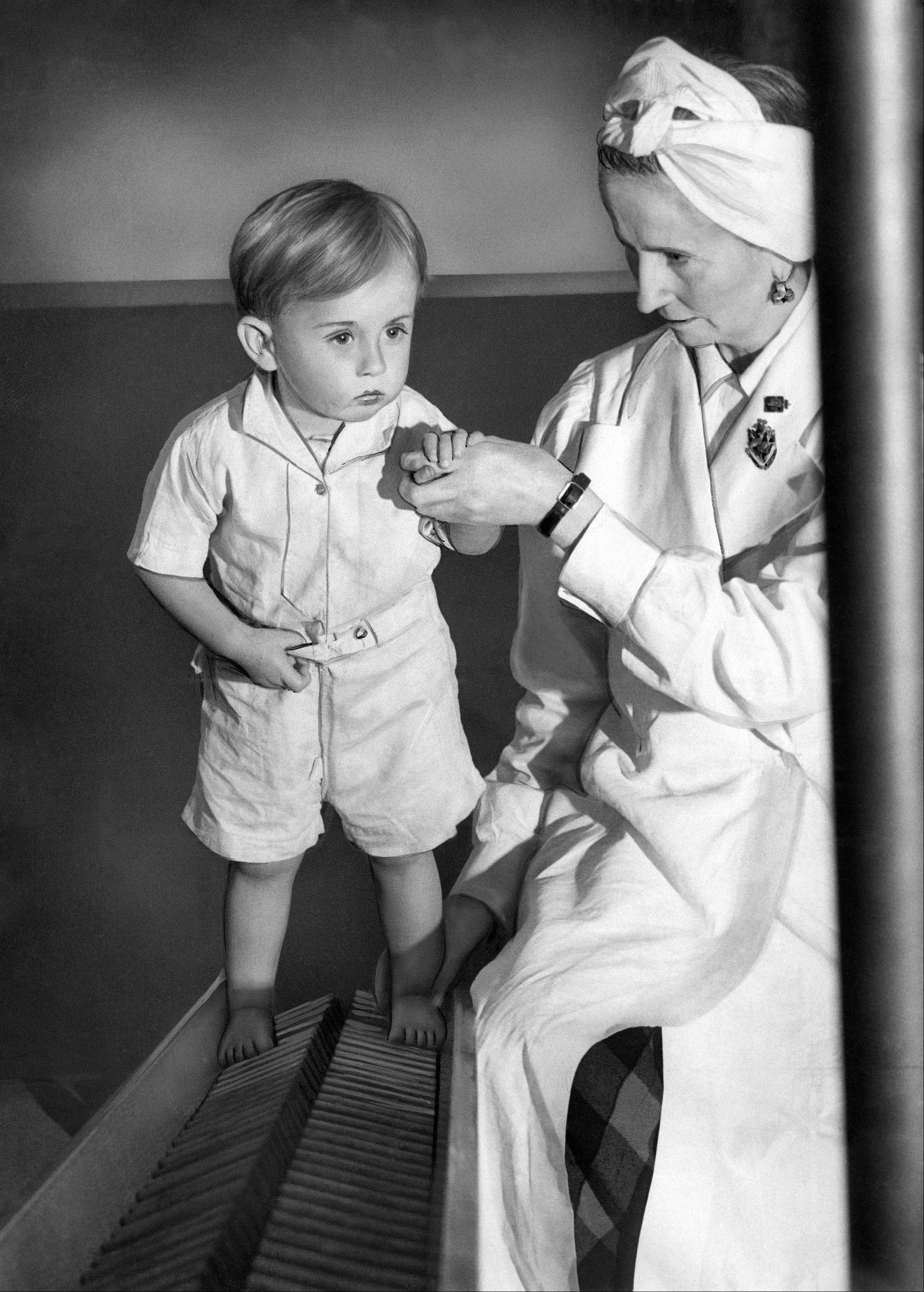 In this June 3, 1943, file photo, physical therapist Estrid Dane carefully supports two-year-old Anthony Bull, seen here walking up a corrugated ladder during exercises which are designed to strengthen his legs in East London. Rickets, the childhood disease that once caused an epidemic of bowed legs and curved spines is making a shocking comeback in Britain.