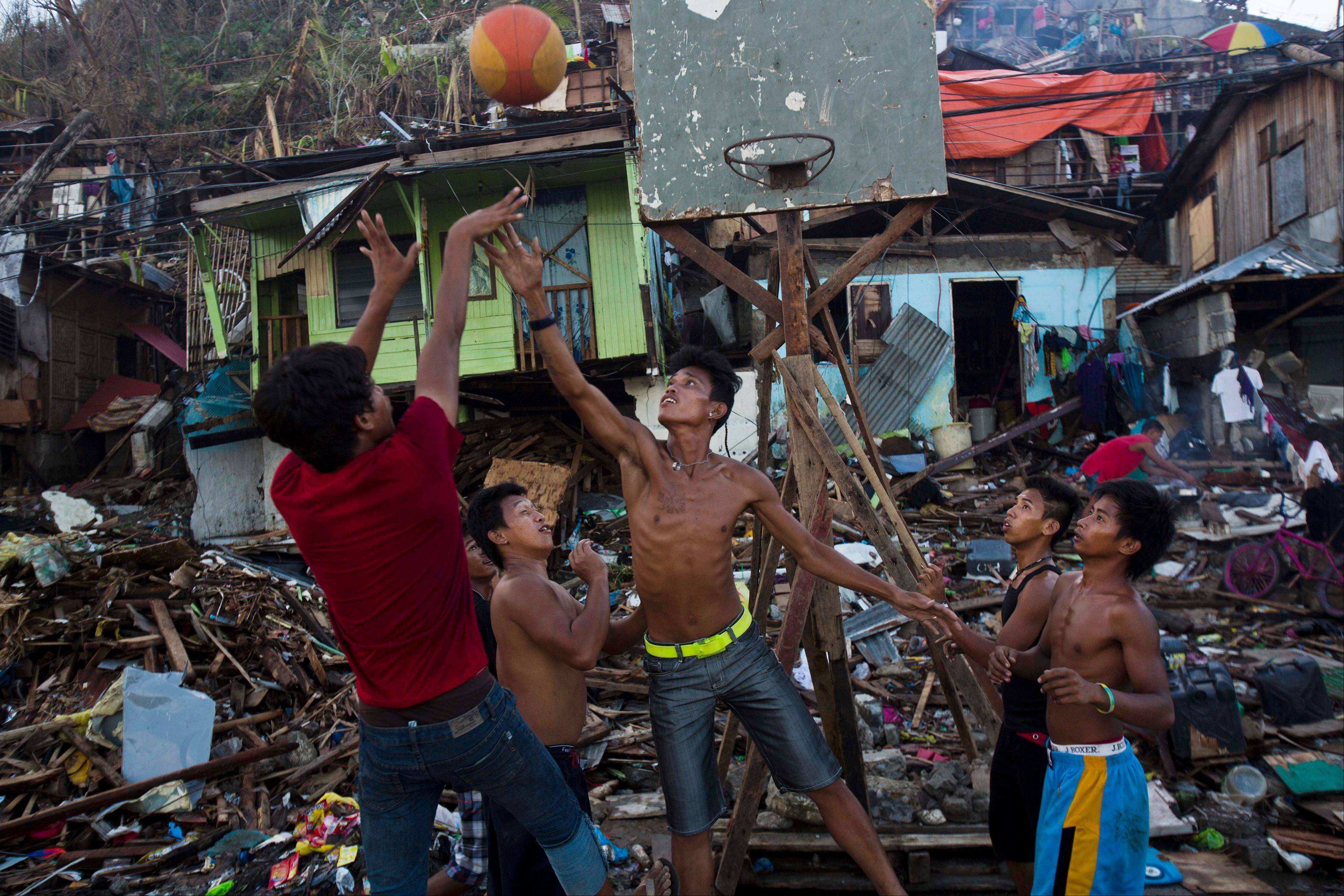 Typhoon Haiyan survivors play basketball in a destroyed neighborhood in Tacloban, Philippines. They found the hoop in the ruins of their obliterated neighborhood. They propped up the backboard with broken wood beams and rusty nails scavenged from vast mounds of storm-blasted homes.