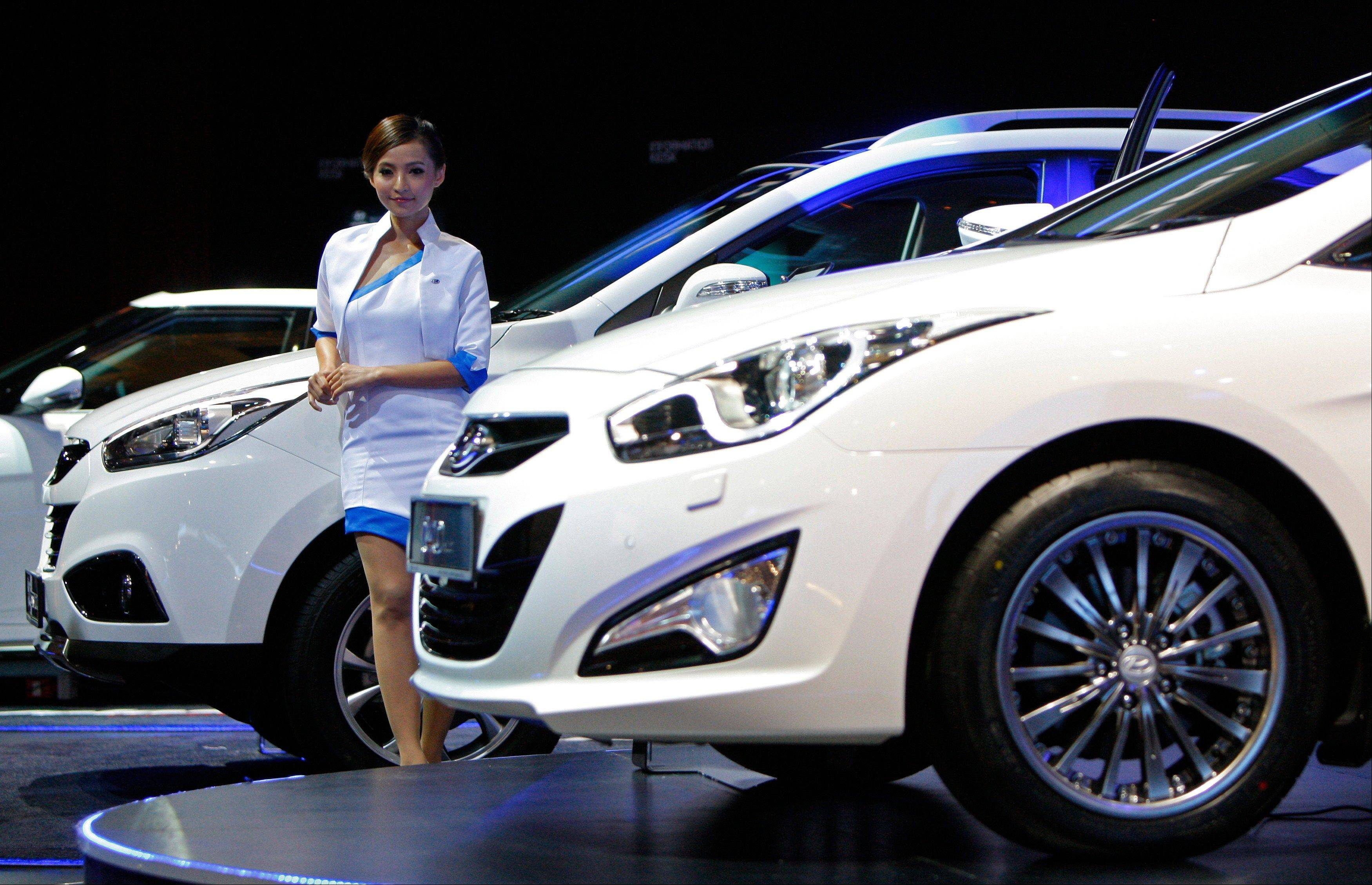 A model poses Sunday next to a Hyundai Tucson facelift on display at the Kuala Lumpur International Motor Show in Kuala Lumpur, Malaysia. In 2014, Hyundai says it will starts selling Tucson SUV powered by a hydrogen fuel cell. It will be the first mass-market vehicle of its type to be sold or leased in the U.S.