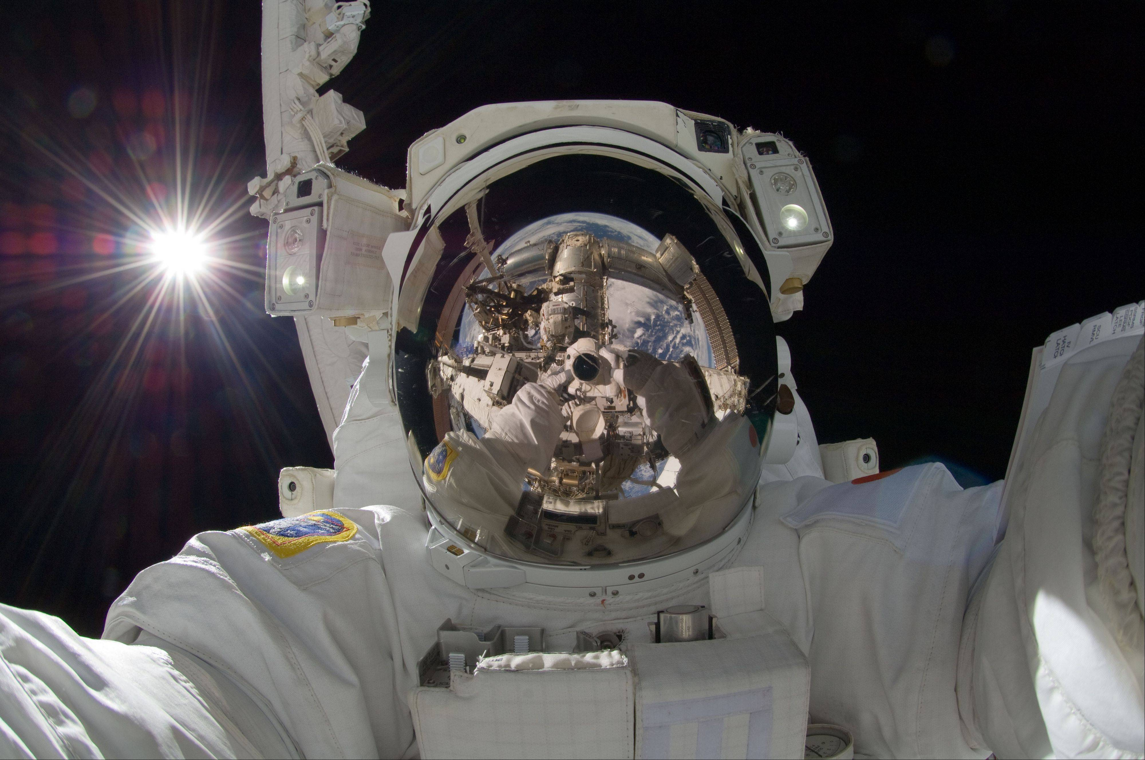 Japan Aerospace Exploration Agency astronaut Aki Hoshide, Expedition 32 flight engineer, uses a digital still camera to expose a photo of his helmet visor during the mission's third session of extravehicular activity (EVA).