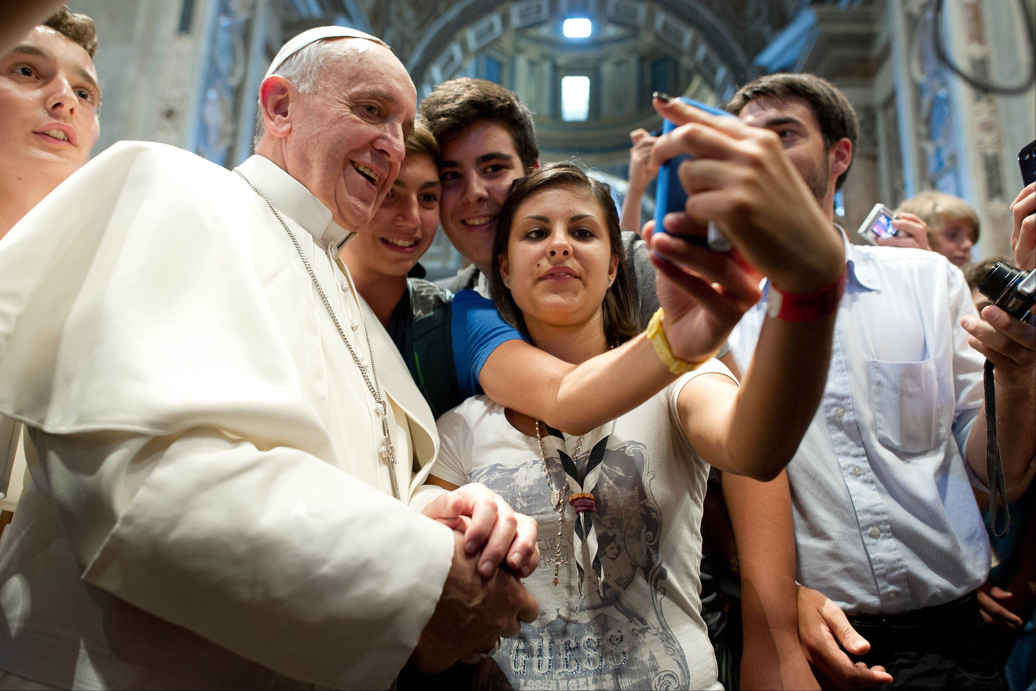 "Pope Francis has his picture taken inside St. Peter's Basilica with youths who came to Rome for a pilgrimage, at the Vatican, Wednesday, Aug. 28, 2013. ""Selfie"" the smartphone self-portrait has been declared word of the year for 2013 by Britain's Oxford University Press."