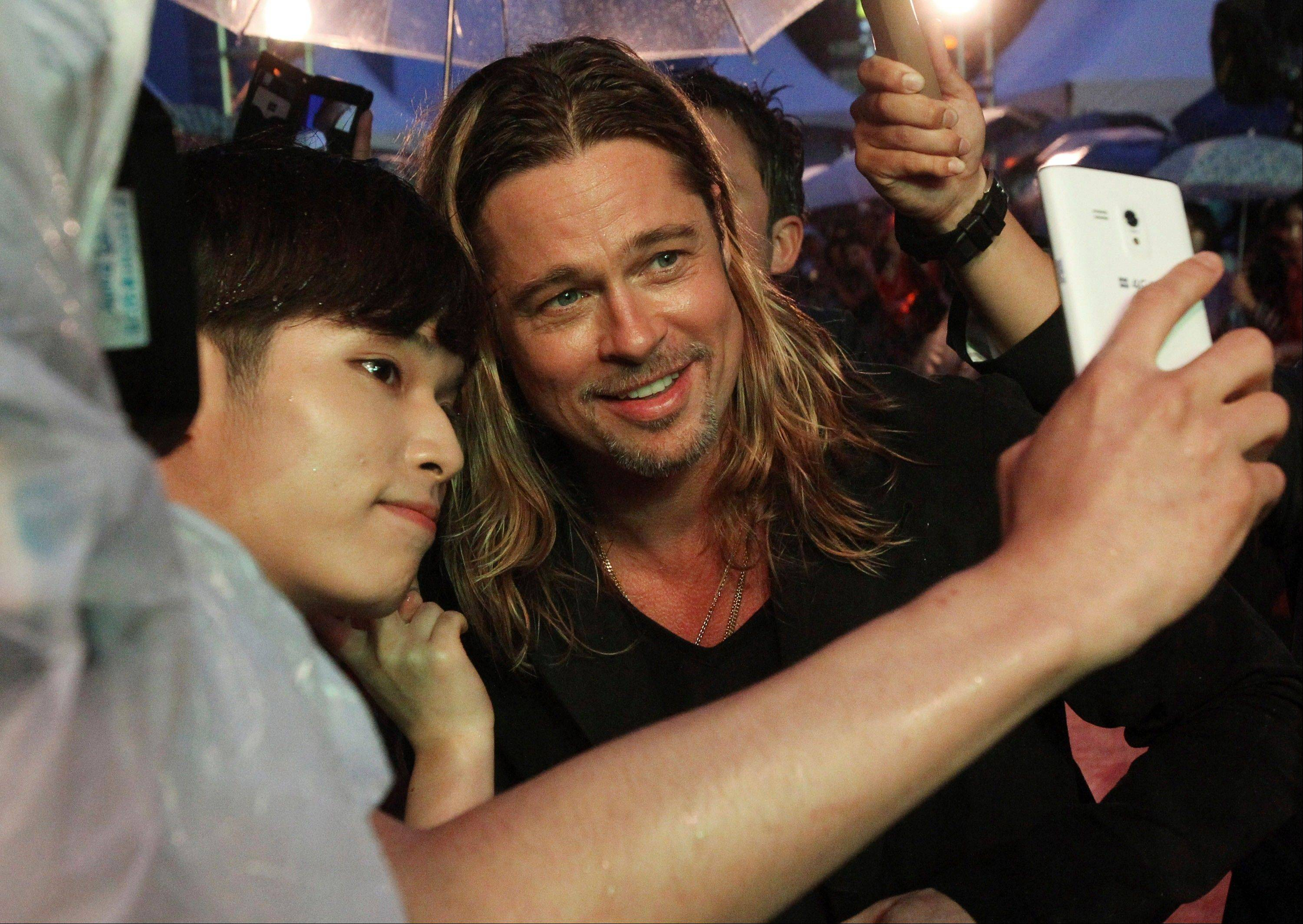 "Brad Pitt poses for a photo with a fan in Seoul. ""Selfie"" the smartphone self-portrait has been declared word of the year for 2013 by Britain's Oxford University Press."