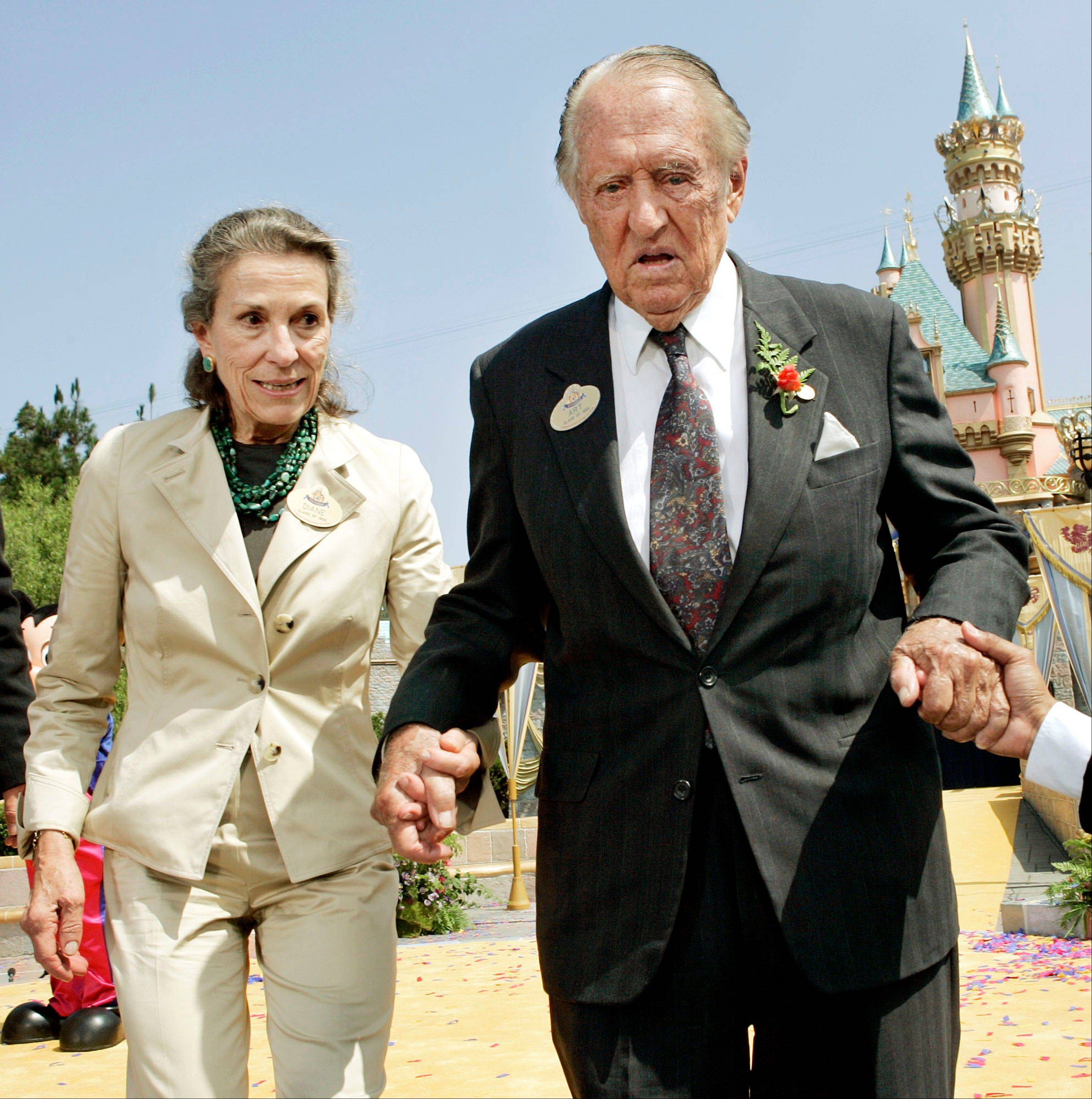 In this July 17, 2005 file photo, Diane Disney Miller, left, assists Art Linkletter, who fifty years earlier hosted the live opening day telecast of Disneyland, as they depart the podium following a re-dedication ceremony in Anaheim, Calif. Disney Miller, the daughter of Walt Disney and one of his inspirations for building the Disneyland theme park, has died at her home in Napa, California. She was 79.