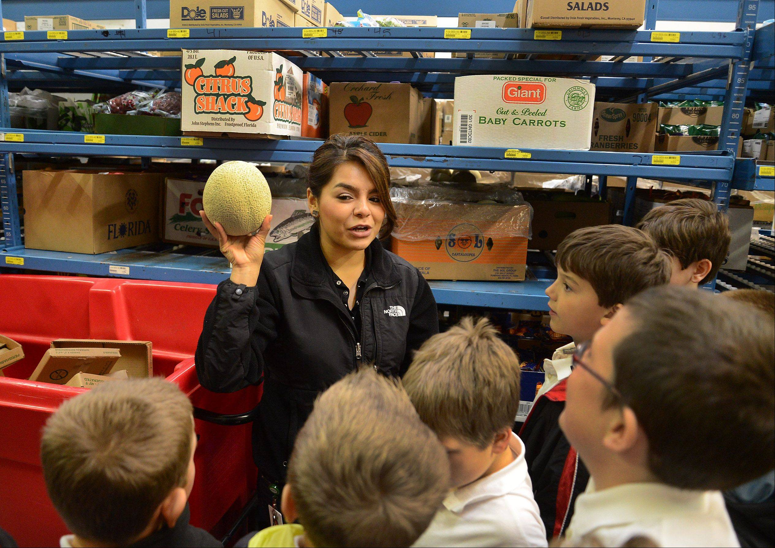 Carina Gonzalez, Peapod's operations trainer and development specialist, leads a group of St. Francis de Sales School fourth-graders on a tour of the company's Lake Zurich warehouse facility. The students learned how to get the biggest and healthiest bang for their food buck Tuesday, thanks to the Kids Give Back program courtesy of Peapod.
