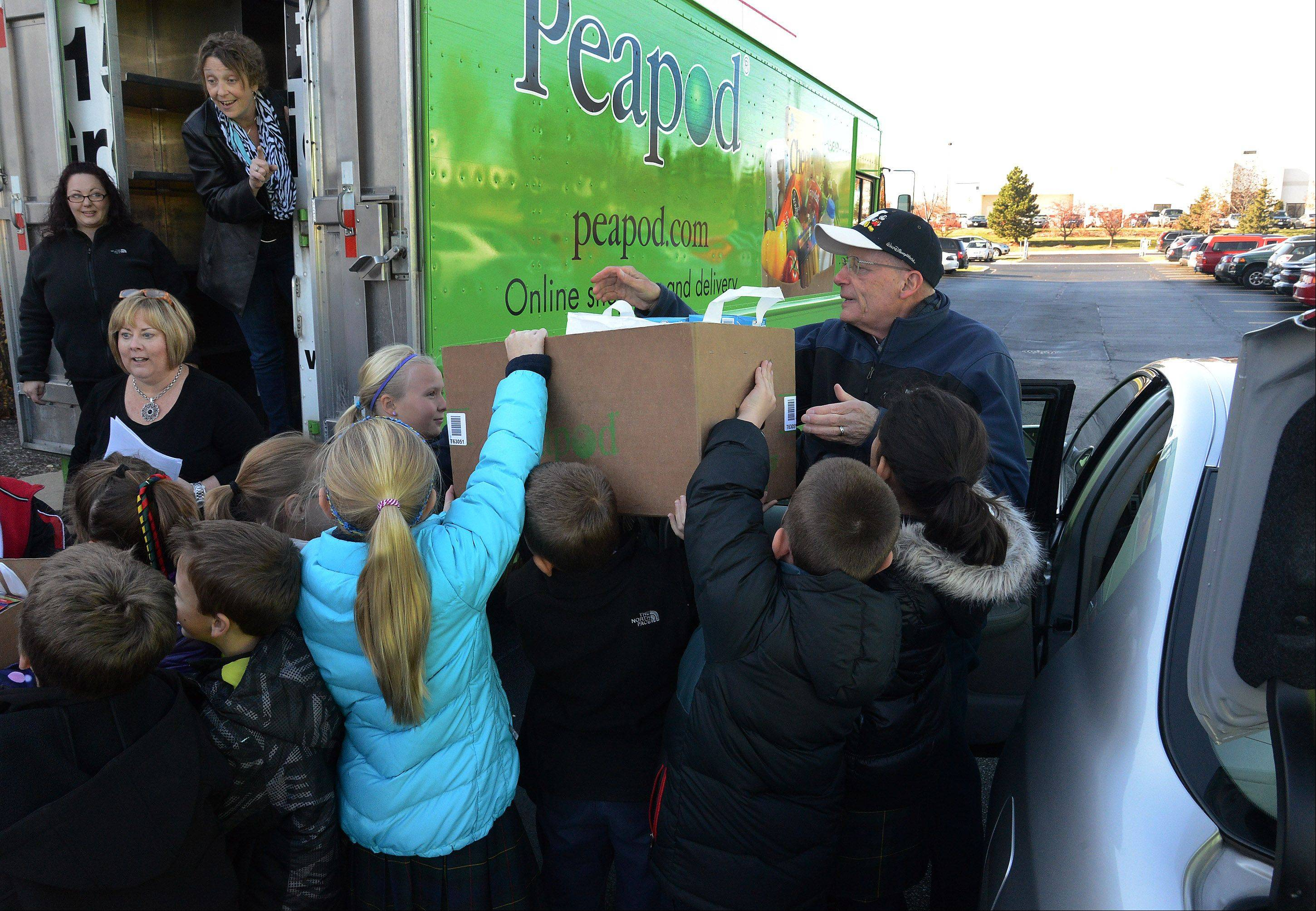 Fourth-graders from St. Francis de Sales School help Jim Westney of the St. Vincent de Paul Anti-Hunger Ministry pack his vehicle with food they donated through the Kids Give Back program courtesy of Peapod. The students toured Peapod�s Lake Zurich facility to learn the benefits of fresh food sourcing and storage, and the importance of nutrition in their own diets and making intelligent food choices.
