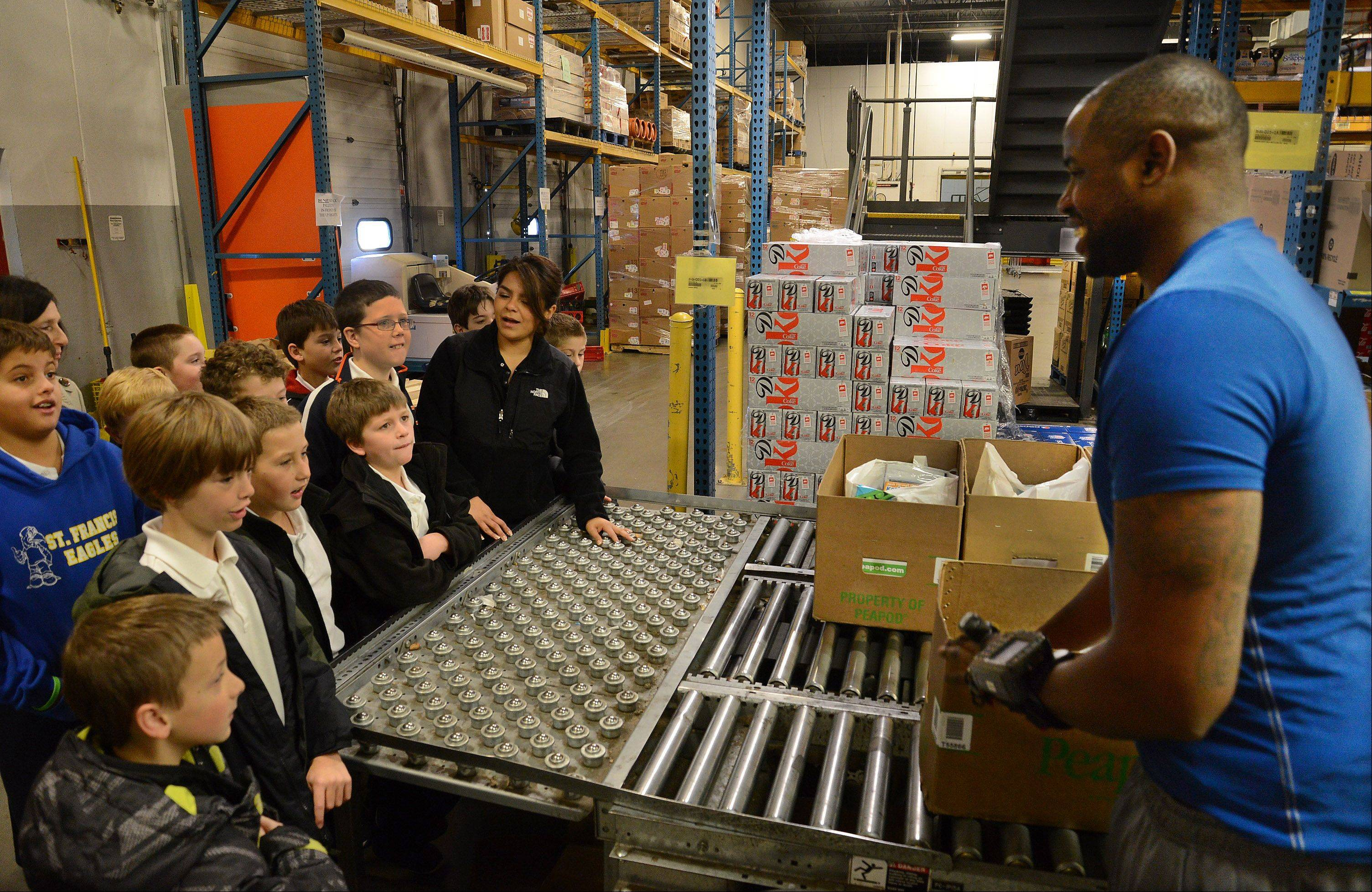 Peapod shopper Monroe Brooks shows how he fills an order in the company's Lake Zurich warehouse, as 50 fourth-graders from St. Francis de Sales School in Lake Zurich learned how to get the biggest and healthiest bang for their food buck Tuesday, as part of the Kids Give Back program courtesy of Peapod.