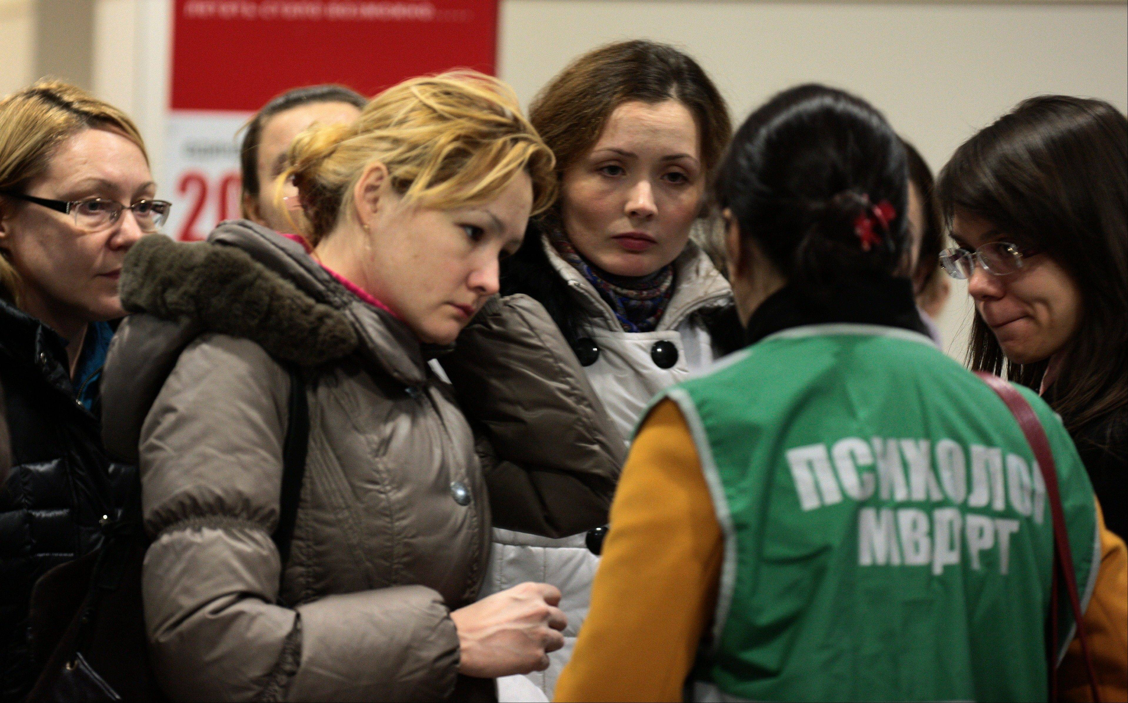 A psychologist at the airport speaks to relatives and friends of those who were aboard the Russian passenger airliner Boeing 737 that crashed in Kazan, about 450 miles east of Moscow, Sunday, Nov. 17, 2013.