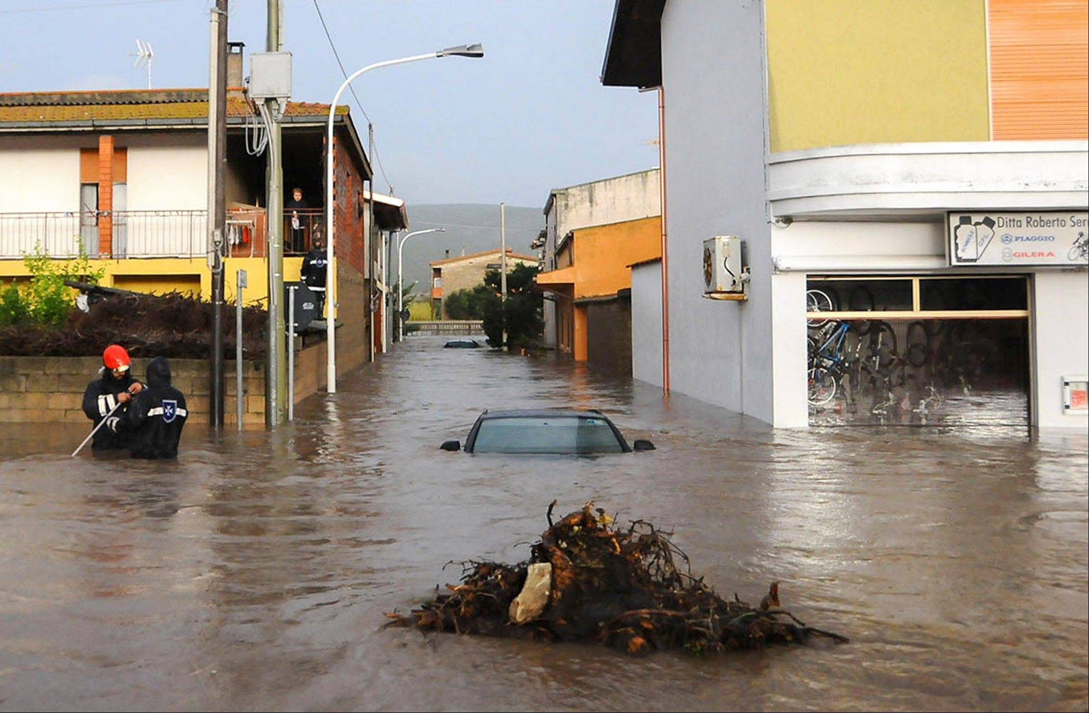 Rescuers work in a flooded street in the small town of Uras, Sardinia, Monday, Nov. 18, 2013. A violent rainstorm that flooded entire parts of the Mediterranean island of Sardinia has led to the deaths of at least 17 people.