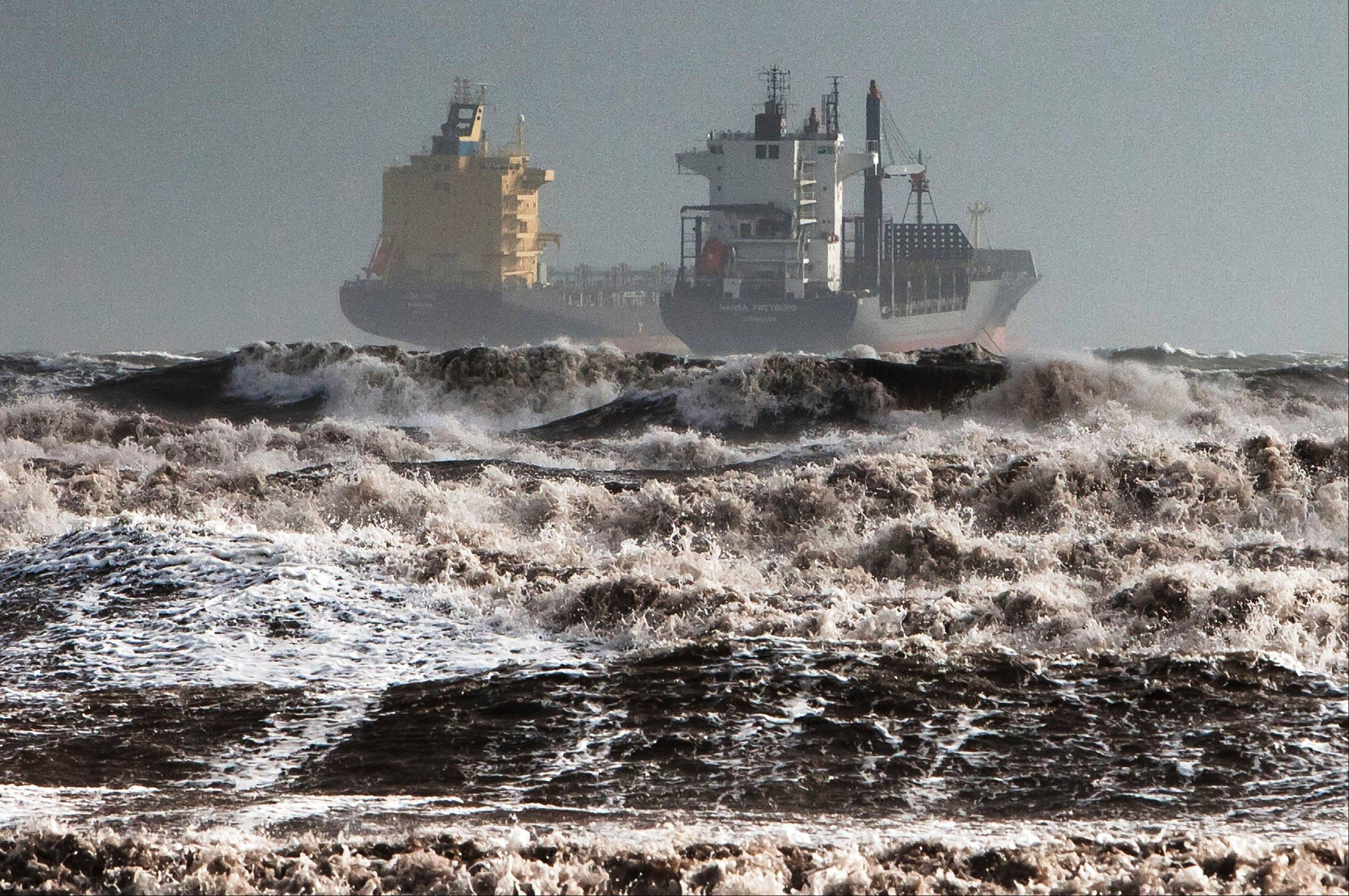 Two tankers are battered by gale winds while at the roadstead in the rough waters of the Gulf of Cagliari, Sardinia, Monday, Nov. 18, 2013. A violent rainstorm that flooded entire parts of the Mediterranean island of Sardinia has led to the deaths of at least 17 people.
