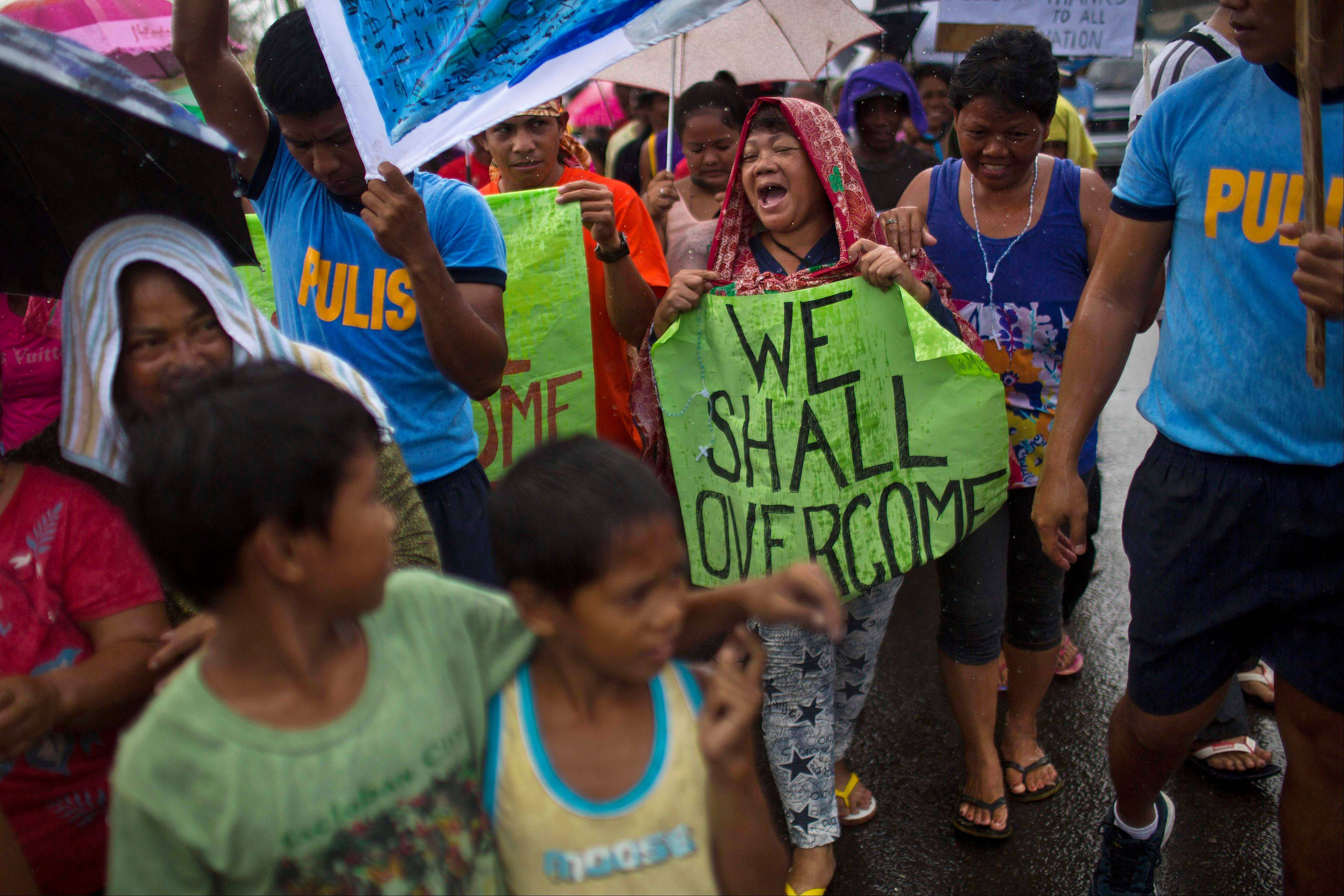 People march in the rain Tacloban, Philippines during a procession to call for courage and resilience among their Typhoon Haiyan survivors on Tuesday Nov. 19, 2013.