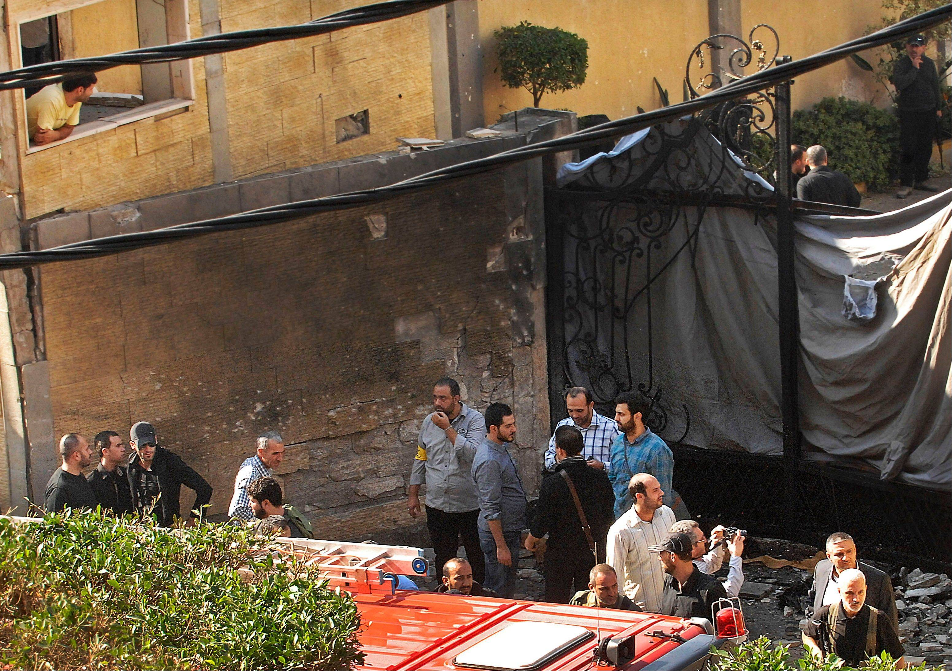 Private security officers gather Tuesday at the damaged entrance of the Iranian Embassy, which was attacked by a suicide bomber, in Beirut, Lebanon. Twin suicide bombings struck outside the Iranian Embassy in the Lebanese capital on Tuesday, killing nearly two dozen, including the Iranian cultural attache, and wounding dozens more in one of the worst bombings to target the predominantly Shiite area in southern Beirut.
