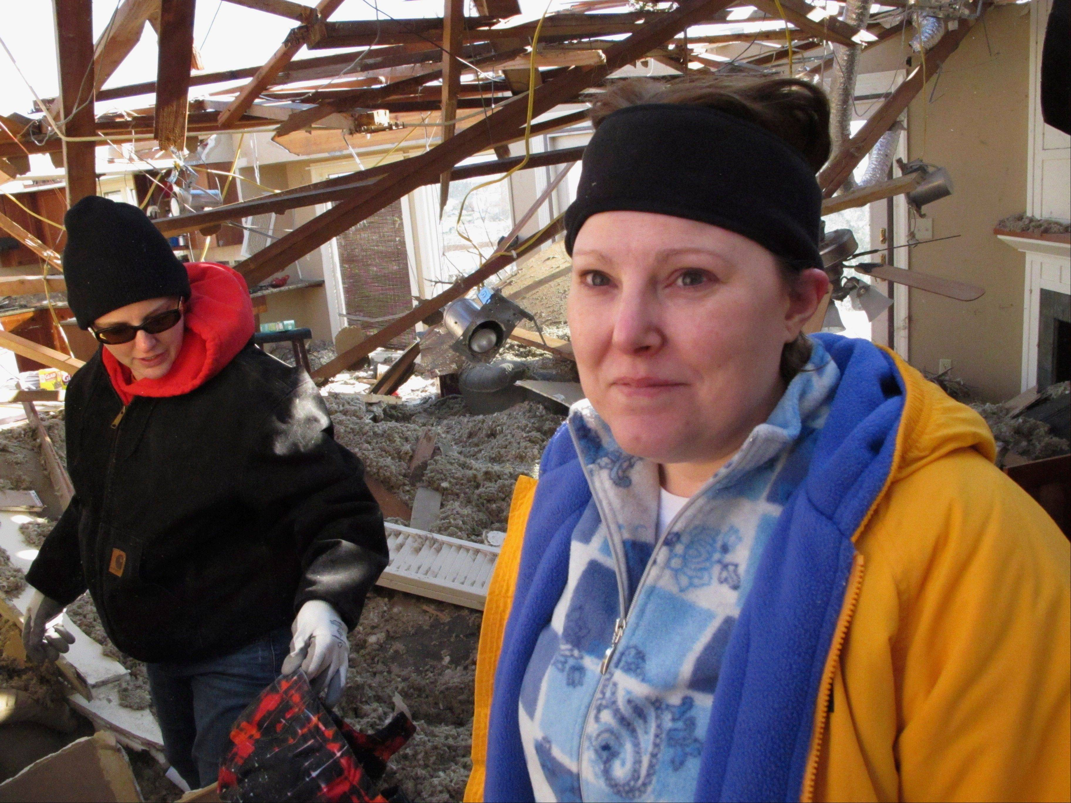 Jessica Bochart, right, works with friends and relatives Monday to dig through the wreckage of her home in Washington, Ill. The home was one of hundreds in the town hit by a tornado on Sunday. Across this Washington neighborhood, homeowners and their friends and families worked quickly in a stiff, cold breeze. Some picked through little more than piles of brick, drywall and lumber. Others, like Bochart, had sections of their houses still standing.