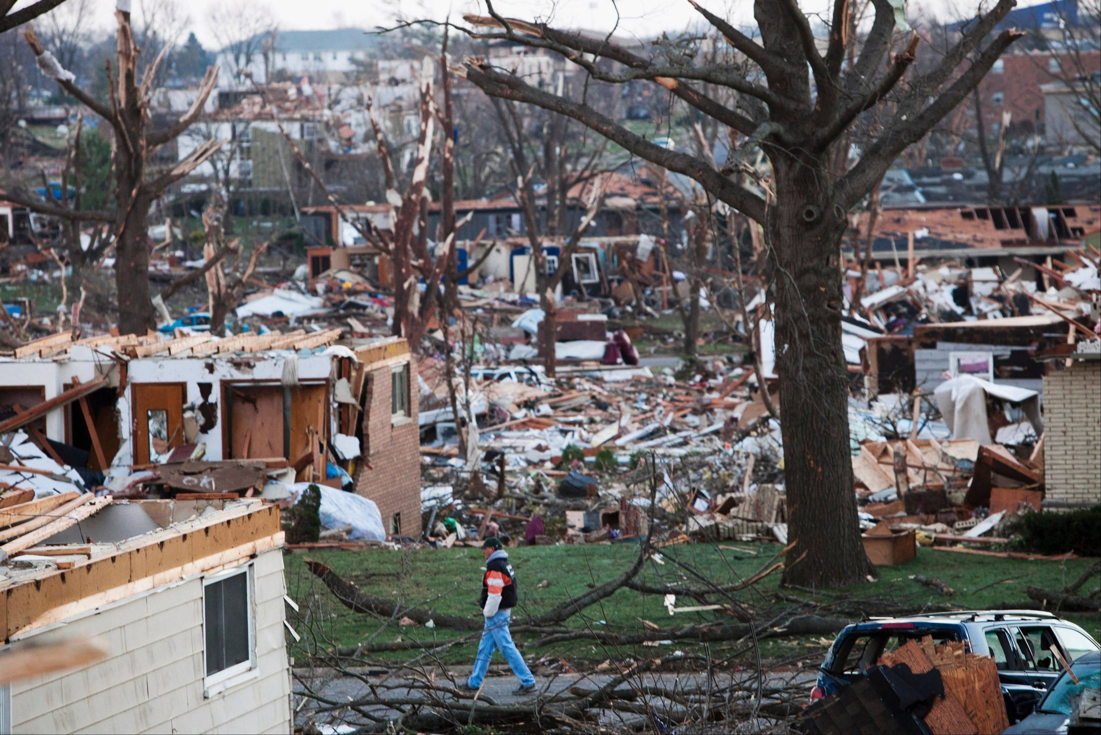 A man walks through what is left of a neighborhood in Washington, a day after a tornado ripped through the central Illinois town. The tornado cut a path about an eighth of a mile wide from one side of Washington to the other and damaged or destroyed as many as 500 homes.