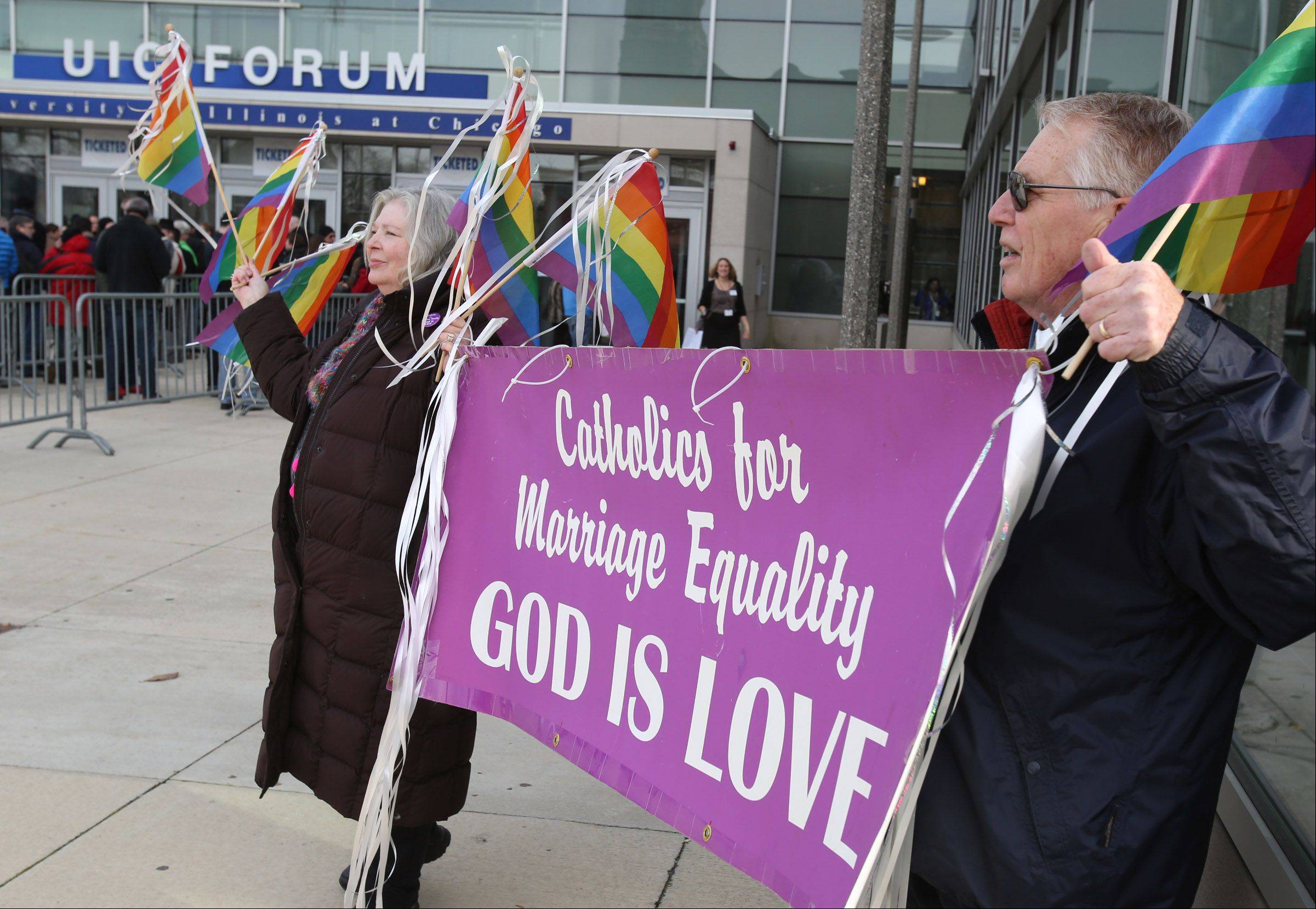 Barbara Marian and Jerry Powers, both of Harvard, hold a sign on behalf of Catholics for Marriage Equality outside the University of Illinois at Chicago Forum, where Gov. Pat Quinn signed a bill legalizing same-sex marriage.