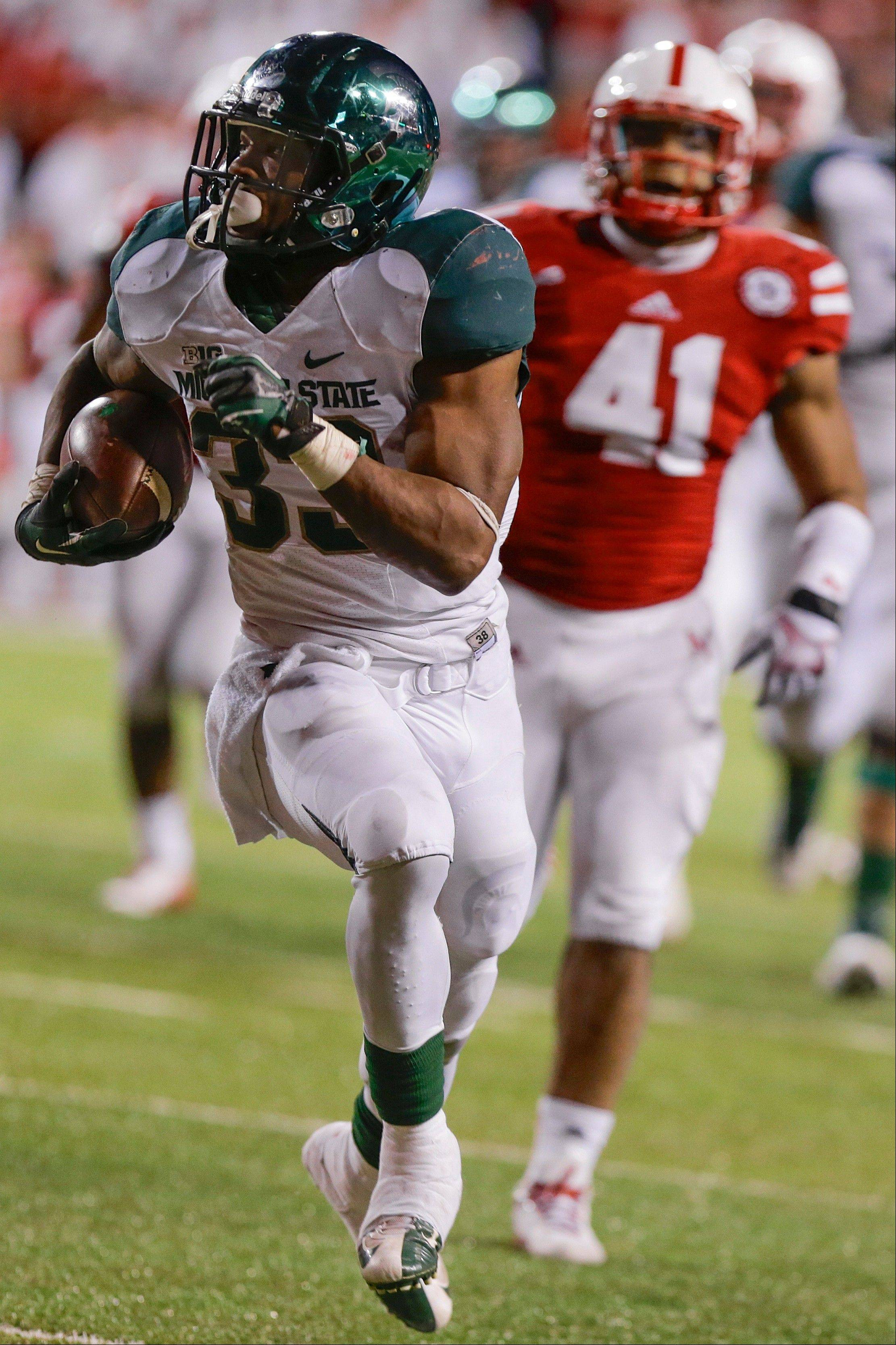 Michigan State running back Jeremy Langford runs for a touchdown while pursued by Nebraska linebacker David Santos last Saturday in Lincoln, Neb.