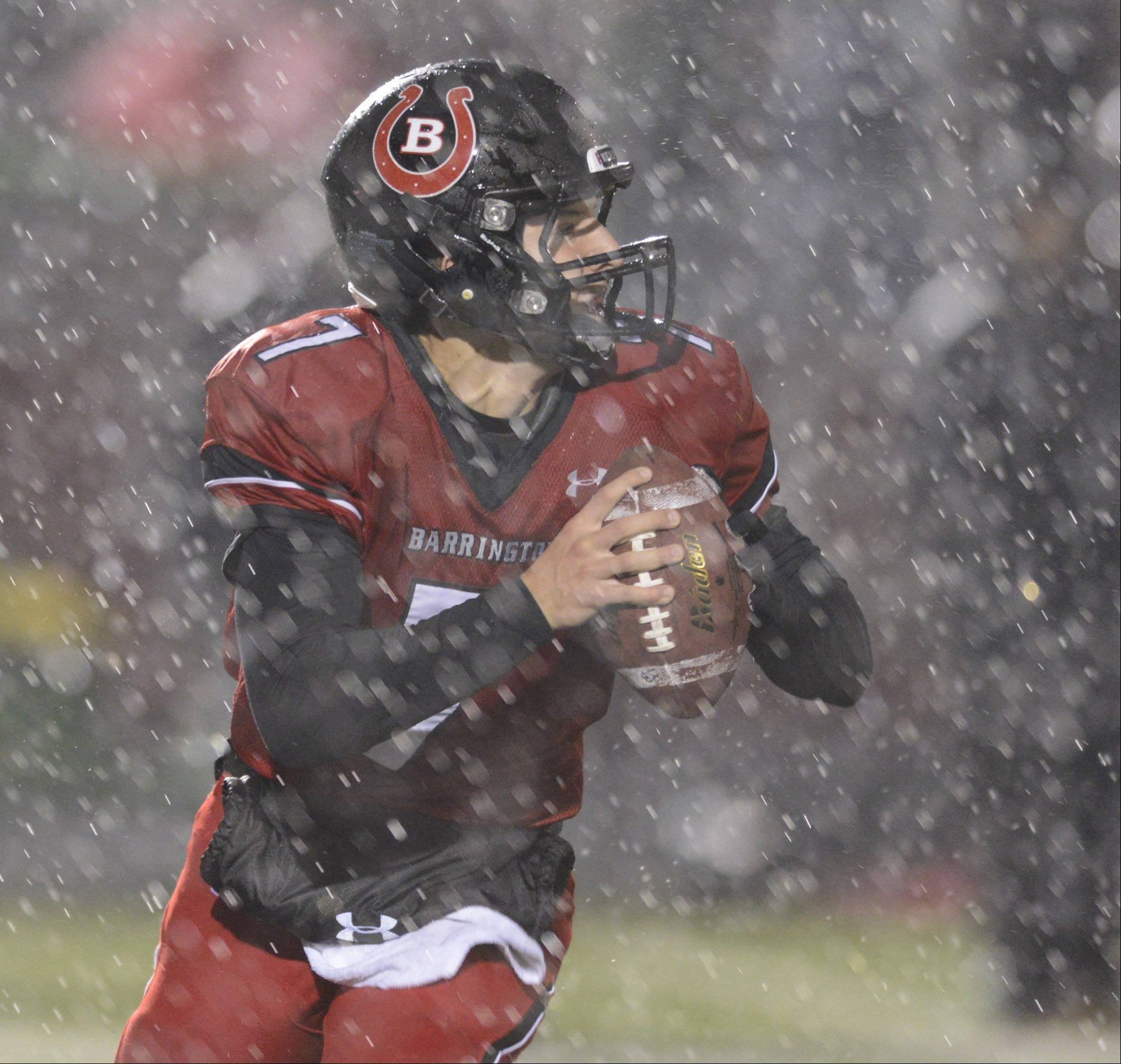 Barrington quarterback Daniel Kubiuk looks for an open teammate in pouring rain during Saturday's Class 8A playoff game against Stevenson.