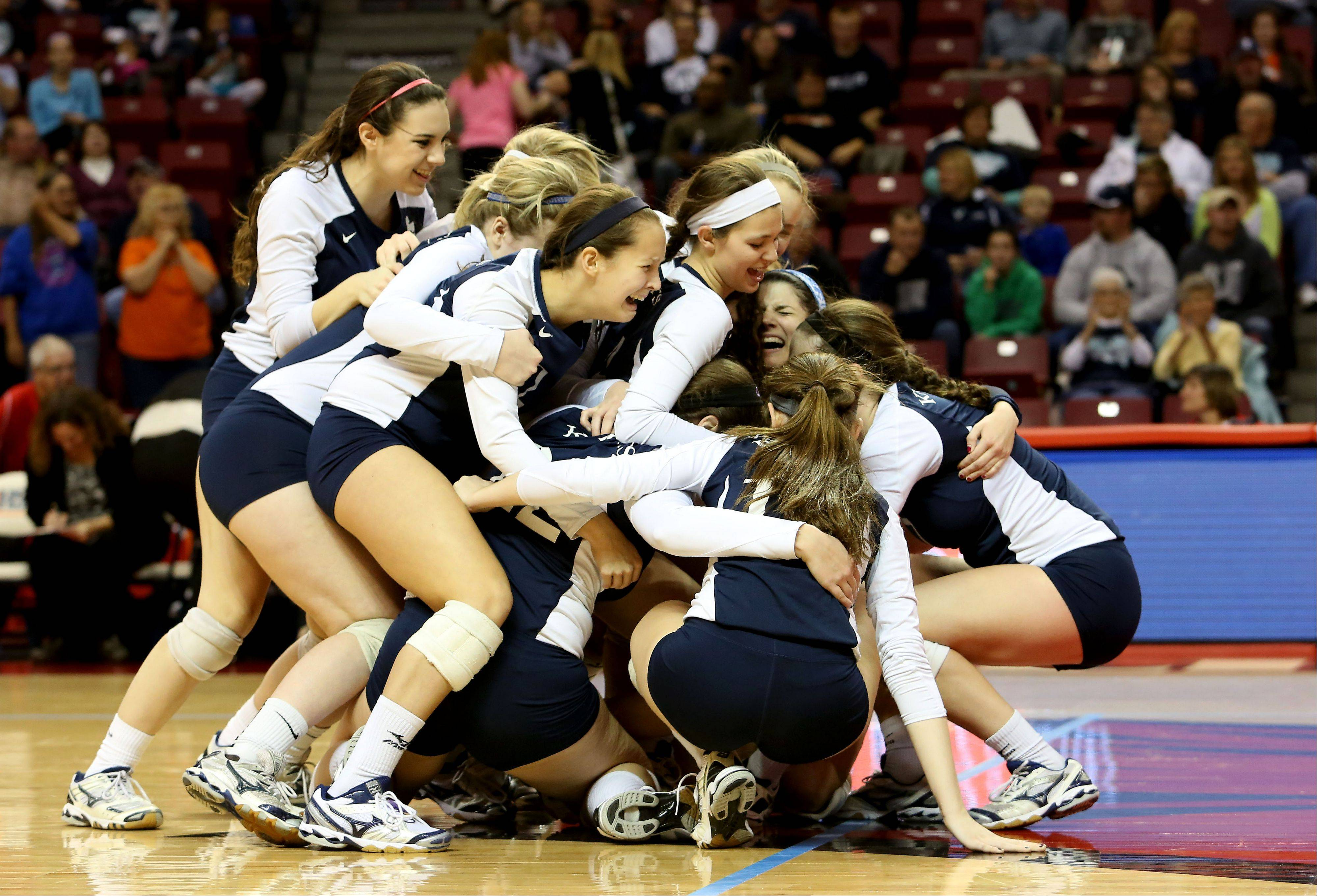 IC Catholic players celebrate after beating Edwards County for the Class 2A volleyball championship Saturday in Normal.