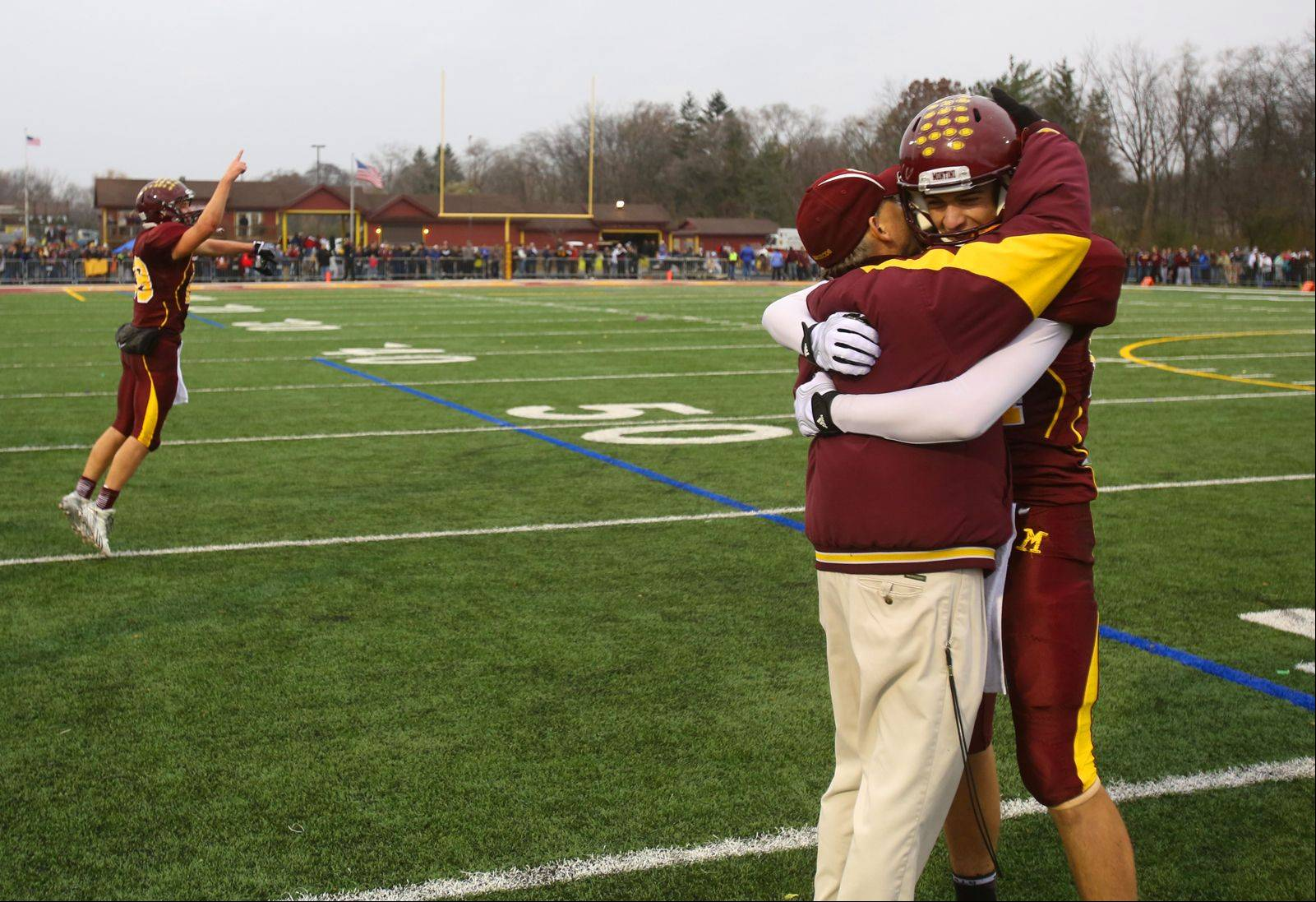 Montini Catholic's Stephen Dennis is congratulated by head coach Chris Andriano after Saturday's game.