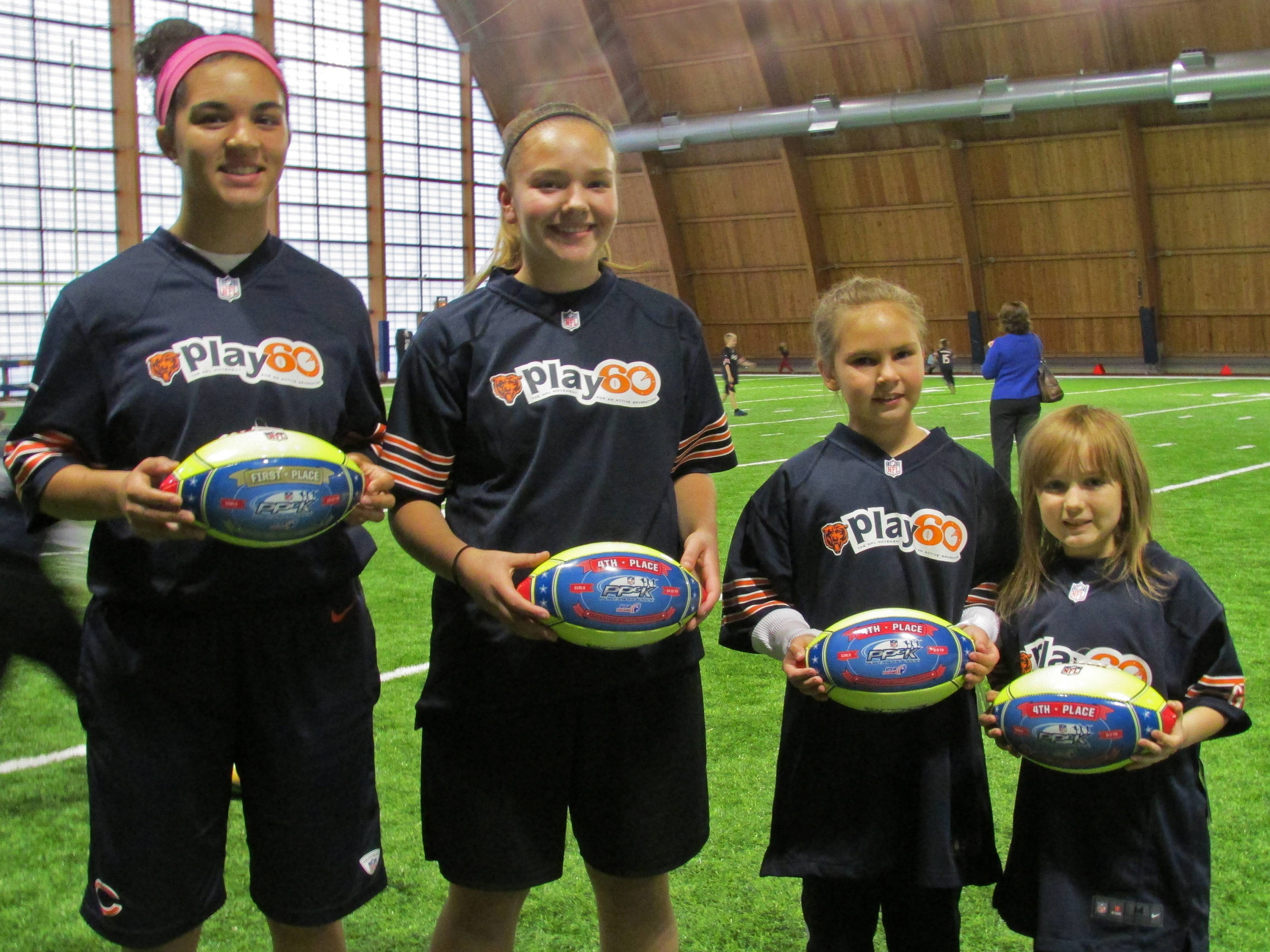 Alisa Fallon, Allison Pearson, Gillian Herman, and Katelyn Dahl hold their prize-winning balls at the Punt, Pass & Kick Team Championships on November 16 at the Walter Payton Center in Lake Forest