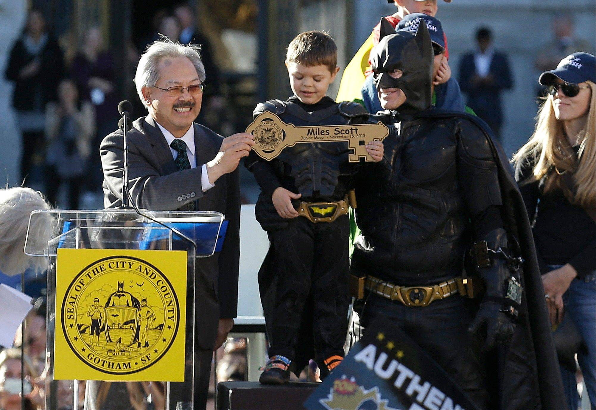 Miles Scott, dressed as Batkid, stands next to Batman as he receives the key to the city from San Francisco Mayor Ed Lee, left, at a rally outside of City Hall in San Francisco, Friday, Nov. 15, 2013. Scott was called into service on Friday morning by San Francisco Police Chief Greg Suhr to help fight crime, as San Francisco turned into Gotham City as city officials helped fulfill the 5-year-old leukemia patient�s wish to be �Batkid,� The Greater Bay Area Make-A-Wish Foundation says.