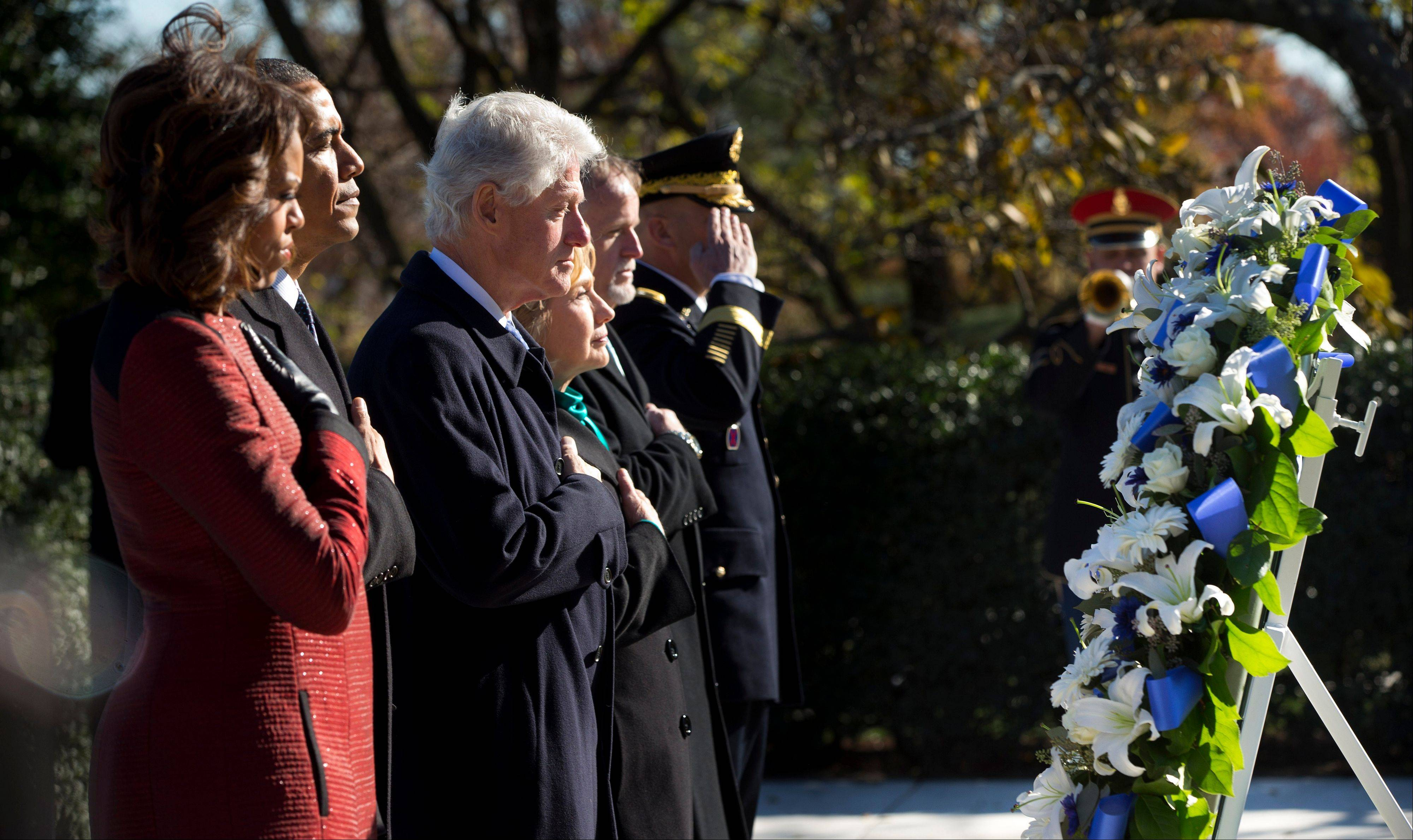President Barack Obama, first lady Michelle Obama, former President Bill Clinton and his wife, former Secretary of State Hillary Rodham Clinton, pause during a wreath laying ceremony in honor of President John F. Kennedy, Wednesday, Nov. 20, 2013, at the JFK gravesite at Arlington National Cemetery in Arlington, Va. Friday will mark the 50th anniversary of the JFK assassination.