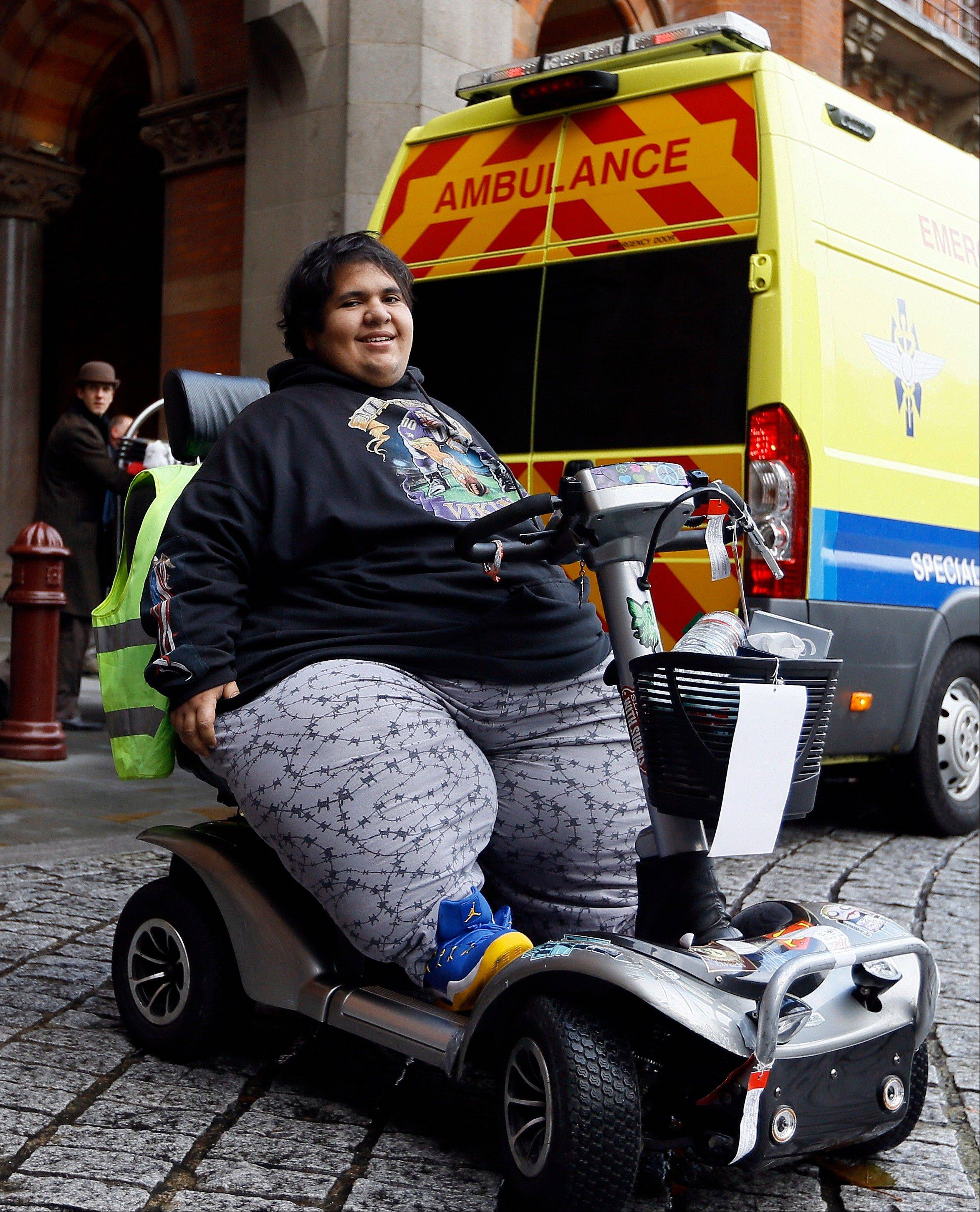 Kevin Chenais sits in his mobility scooter in front of an ambulance at St Pancras in London, Wednesday, Nov. 20, 2013. Chenais, who suffers from a genetic illness, will travel by ambulance and ferry back to France.