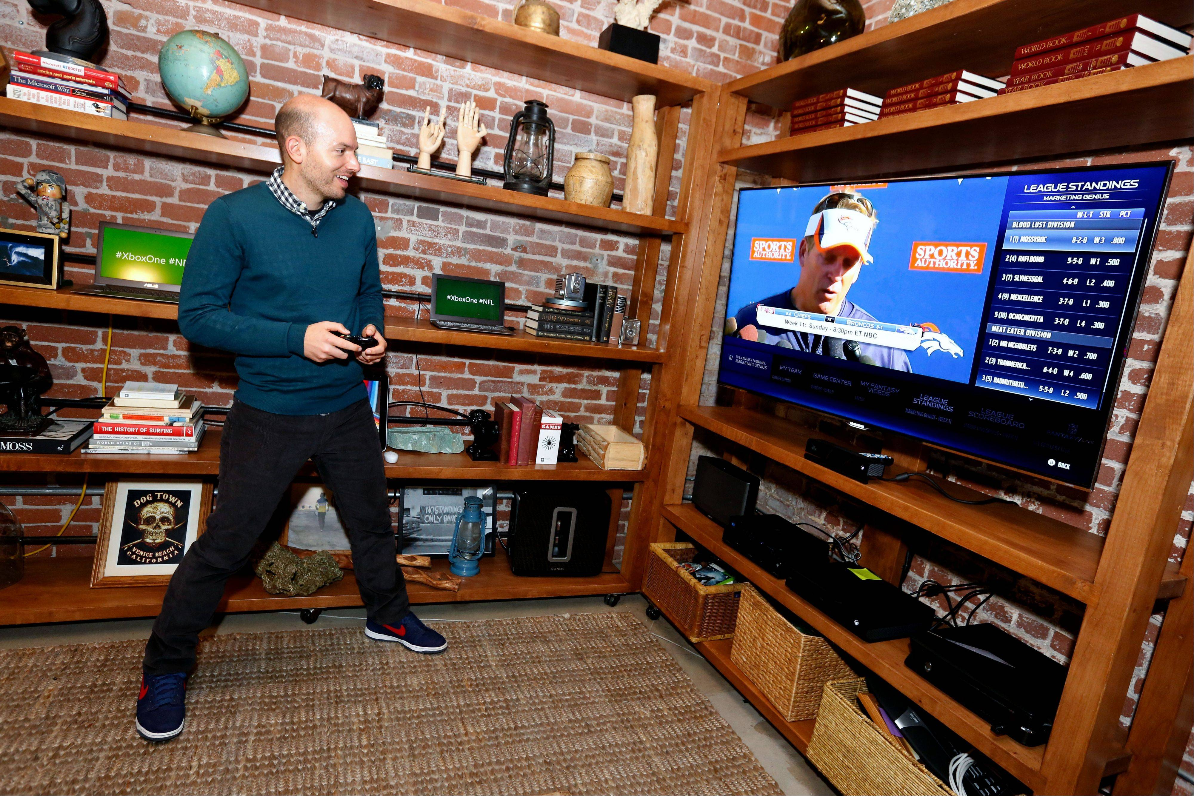 Paul Scheer of The League uses The NFL on Xbox One to check his fantasy team.