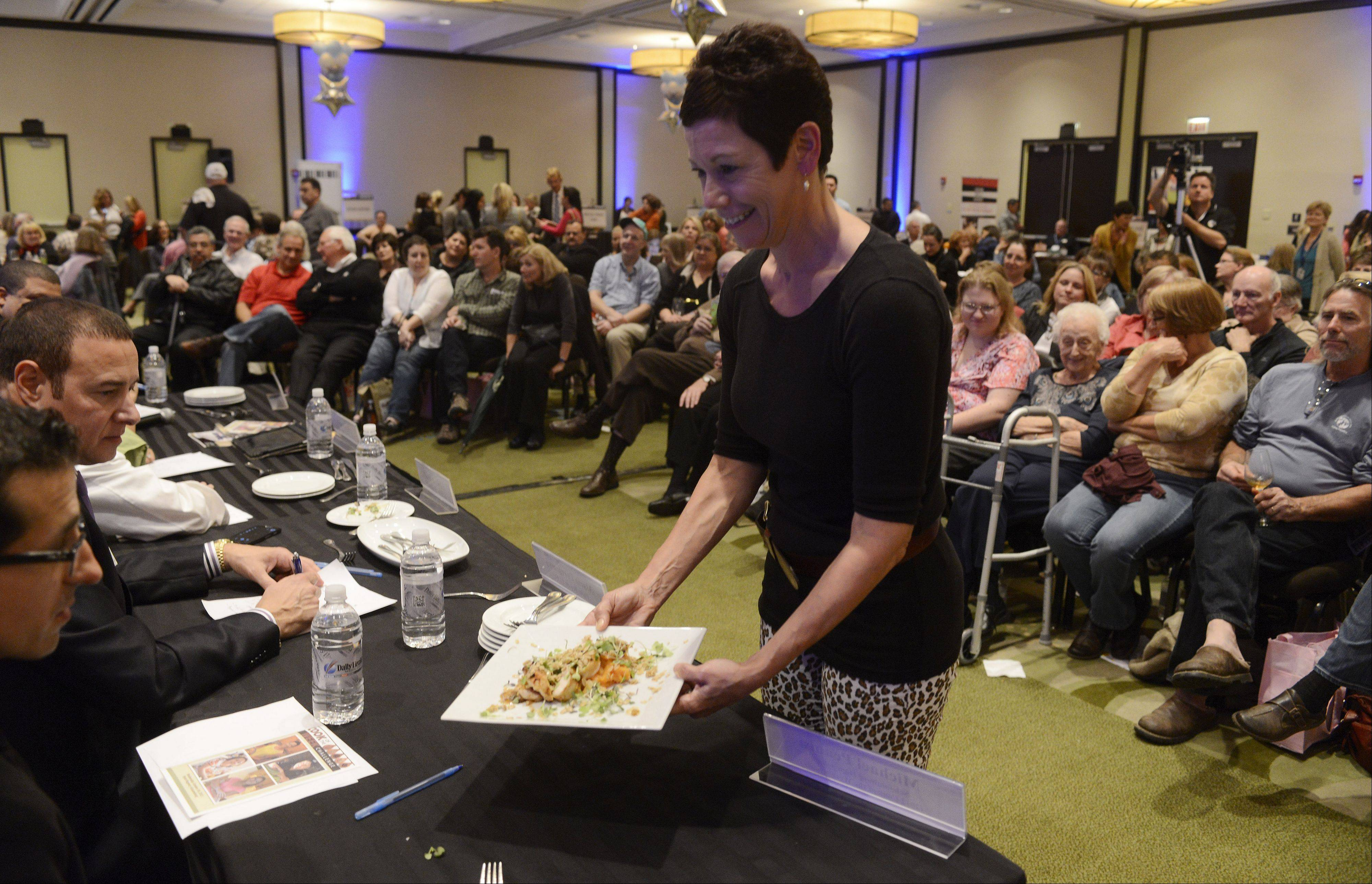 JOE LEWNARD/jlewnard@dailyherald.comLori Motyka of West Chicago presents her dish to the judges during the Daily Herald Cook of the Week Cookoff finals, held at the Hyatt Regency Schaumburg Wednesday.