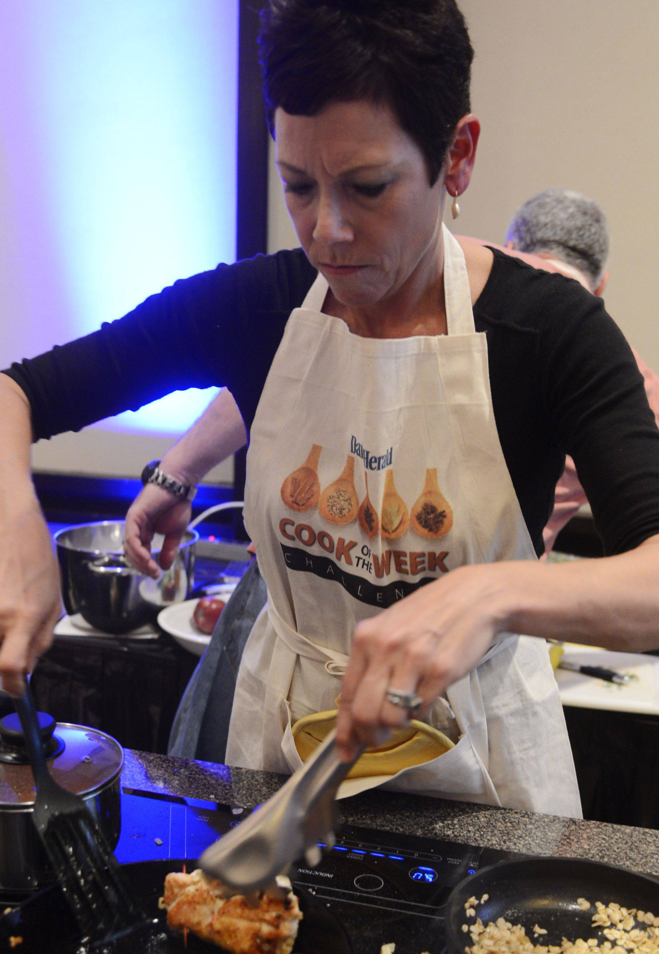 JOE LEWNARD/jlewnard@dailyherald.comLori Motyka of West Chicago turns her chicken during the Daily Herald Cook of the Week Cookoff finals, held at the Hyatt Regency Schaumburg Wednesday.
