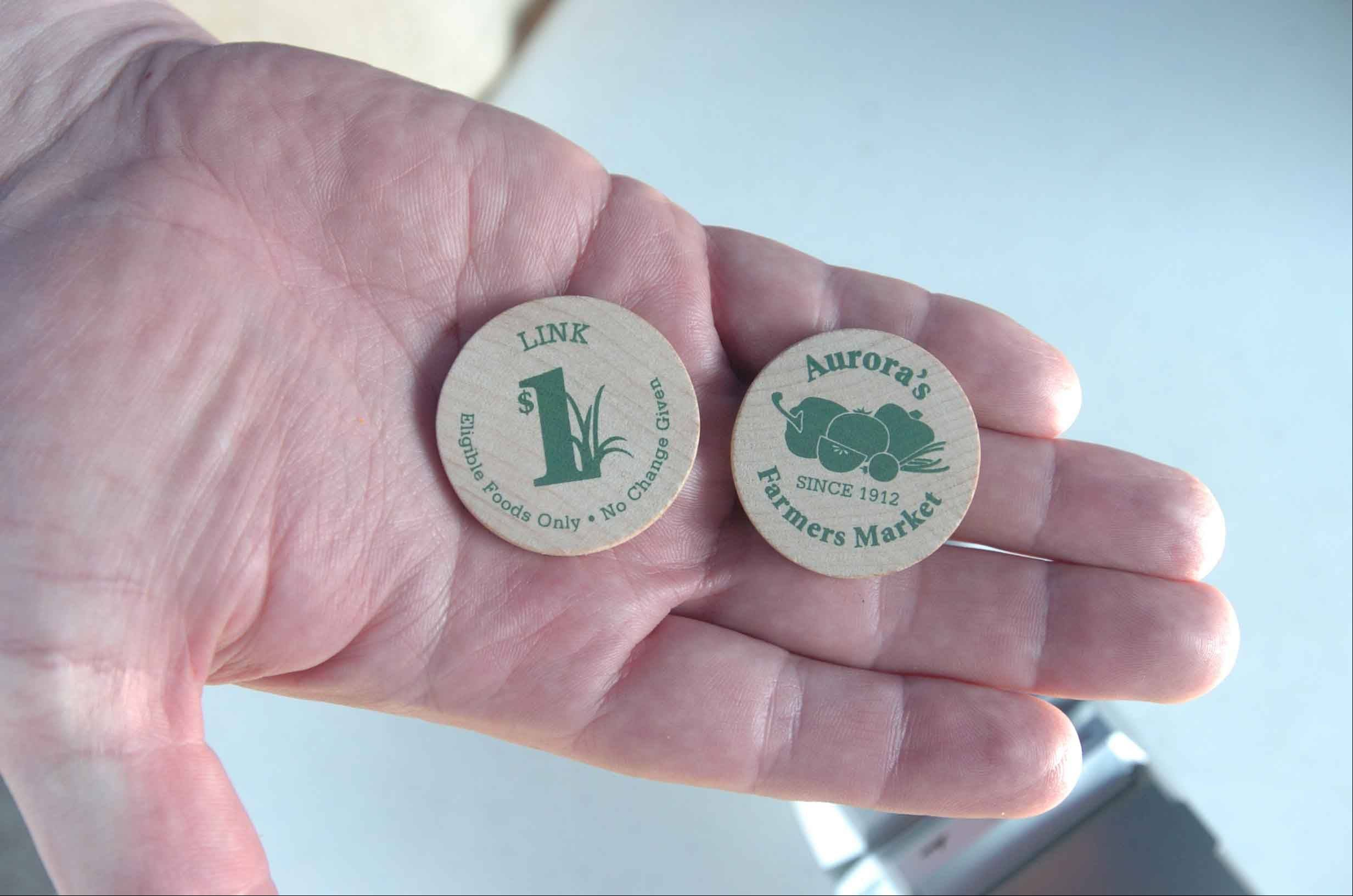 Persons who are using Link food electronic benefits cards are the Aurora Farmers Market purchase these wooden tokens, for $1 or $5, from market organizers and spend them at the individual vendors. The Elgin Downtown Harvest Market uses the same system.