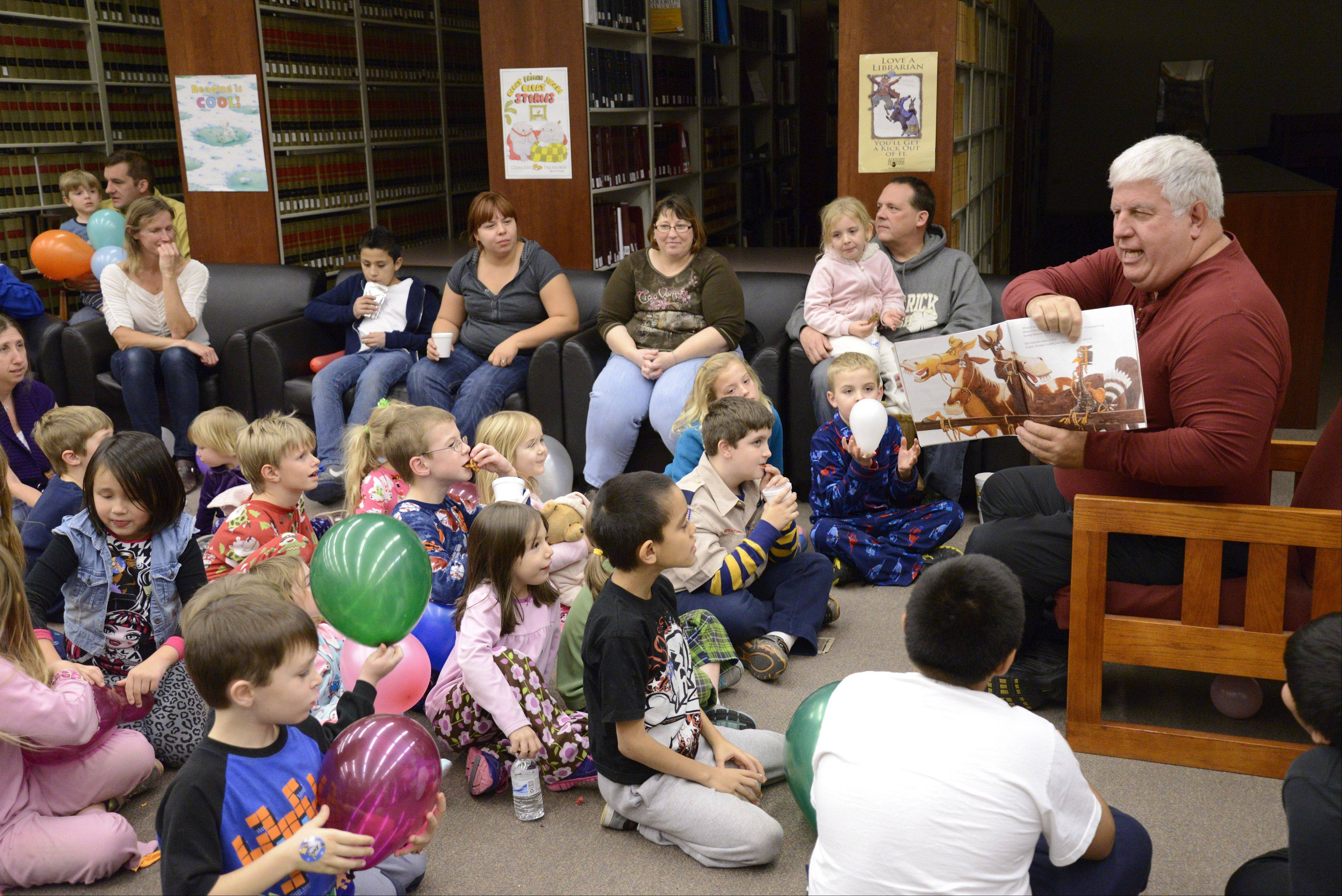 "Kane County Judge David Akemann reads ""Turkey Trouble"" to a full house Wednesday during Family Reading Night at the Kane County Law Library in St. Charles. Judges Rene Cruz and John Dalton joined Akemann to read to more than 40 children and their parents at the 15th annual event."