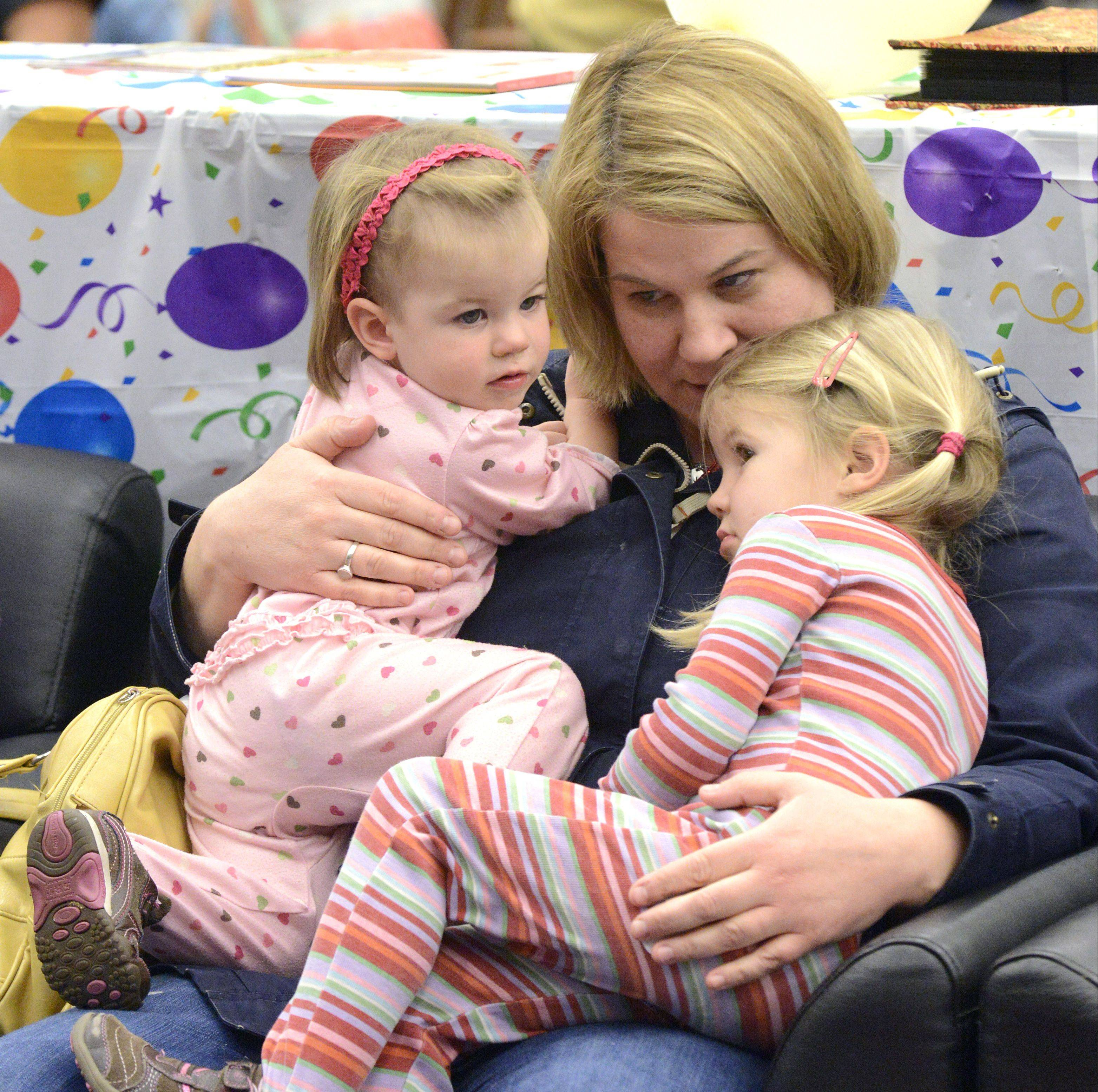 Ann Kennedy of St. Charles cuddles with her children Rose, 15 months, and Grace, 3, while they listen to stories at Family Reading Night. Her other children, James, 7, and Nora, 5, also attended. This is their first time at the event.