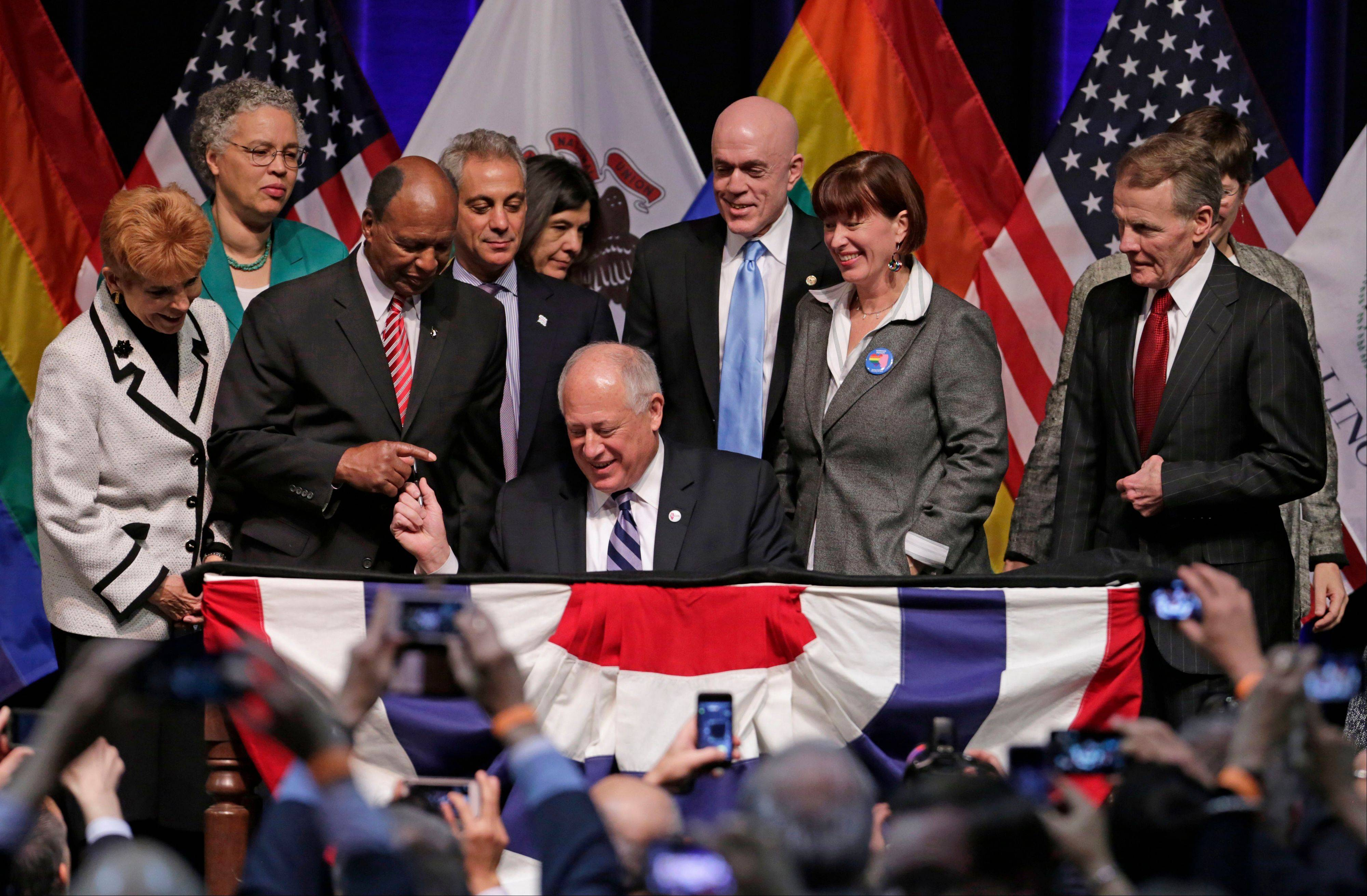 Illinois Gov. Pat Quinn, center, signs the state's Religious Freedom and Marriage Fairness Act into law, making Illinois the 16th state in the nation to embrace full marriage equality for same sex couples.