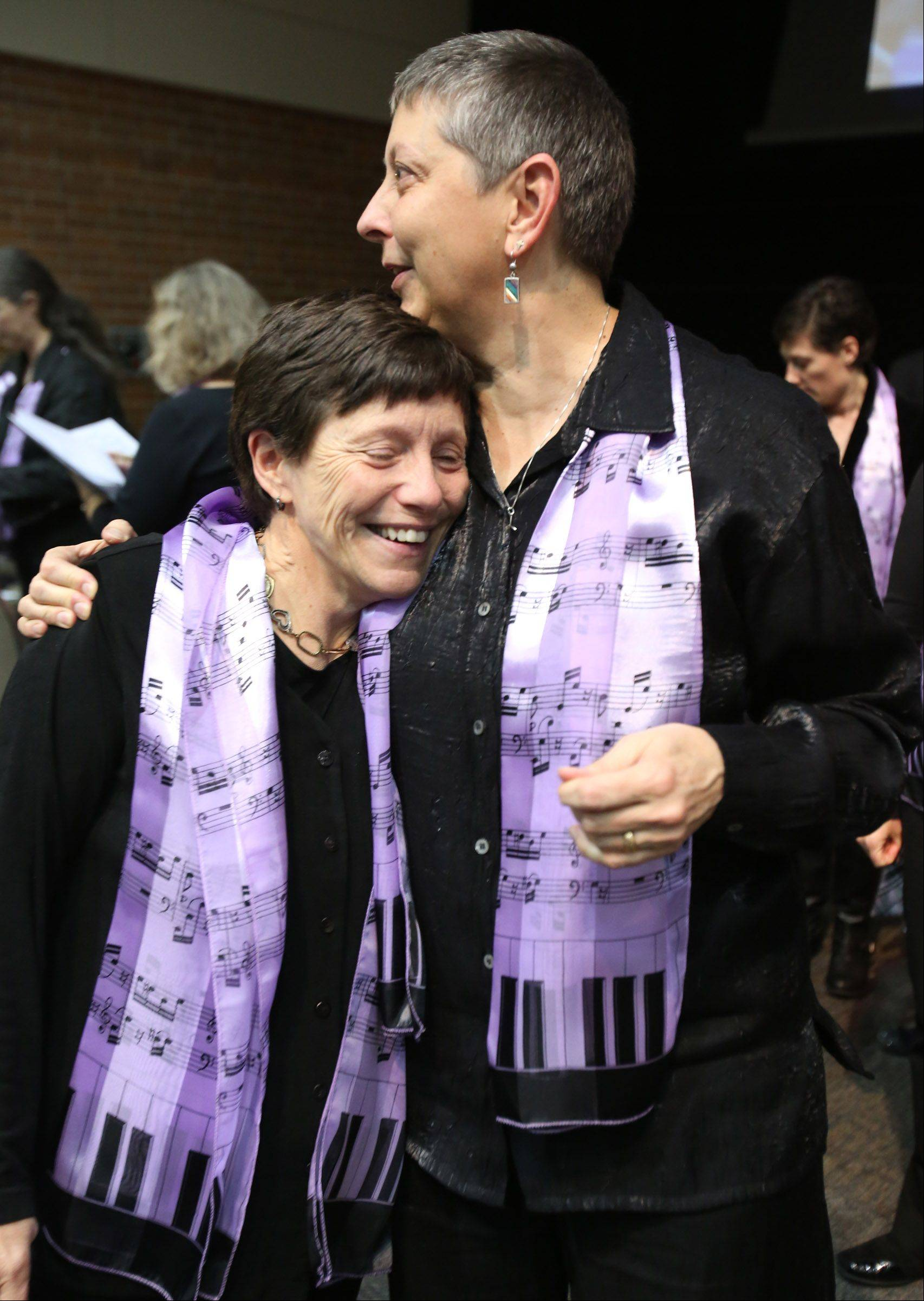 Lou Sutton of Lombard, left, gets a hug from Lois Parr of Chicago. Both sang during the program with Artemis Singers of Chicago, before Gov. Pat Quinn signed the Religious Freedom and Marriage Fairness Act .